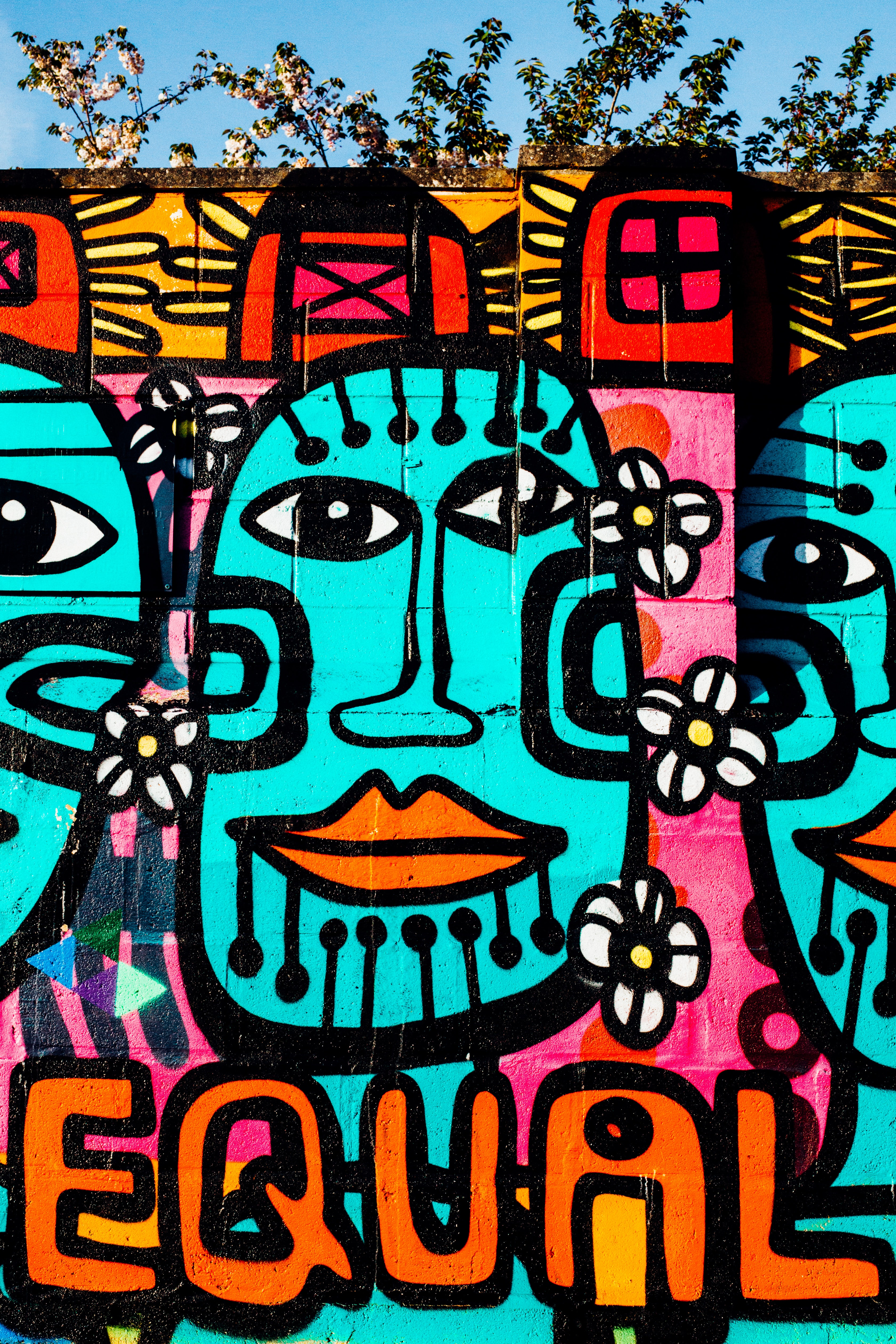 Brightly colored urban graffiti mural artwork on wall with equal text and tribal faces
