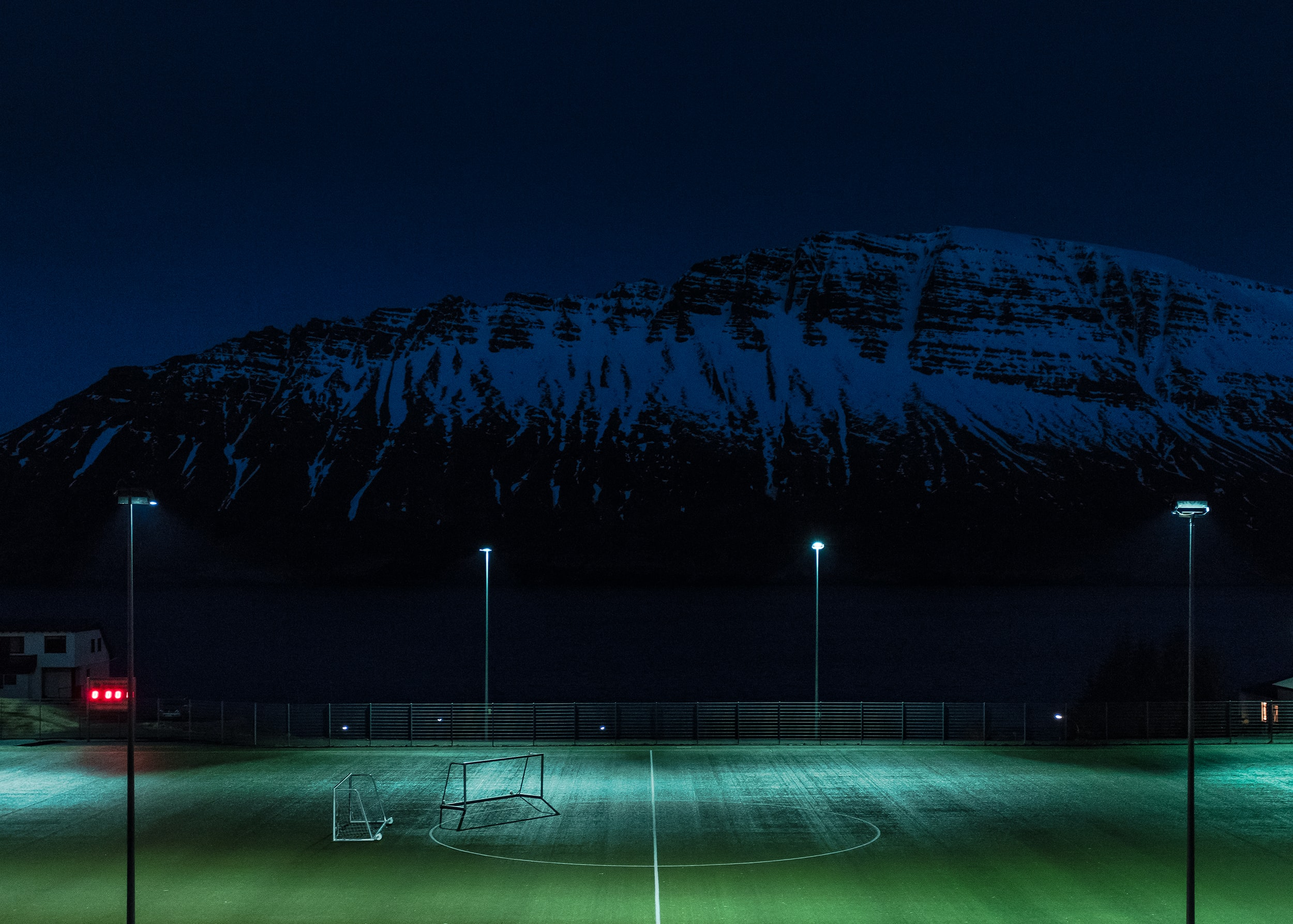 Turf soccer pitch illuminated by floodlights under the snow covered hill at night