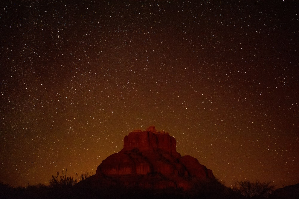 brown mountain under starry sky during nighttime in timelapse photography
