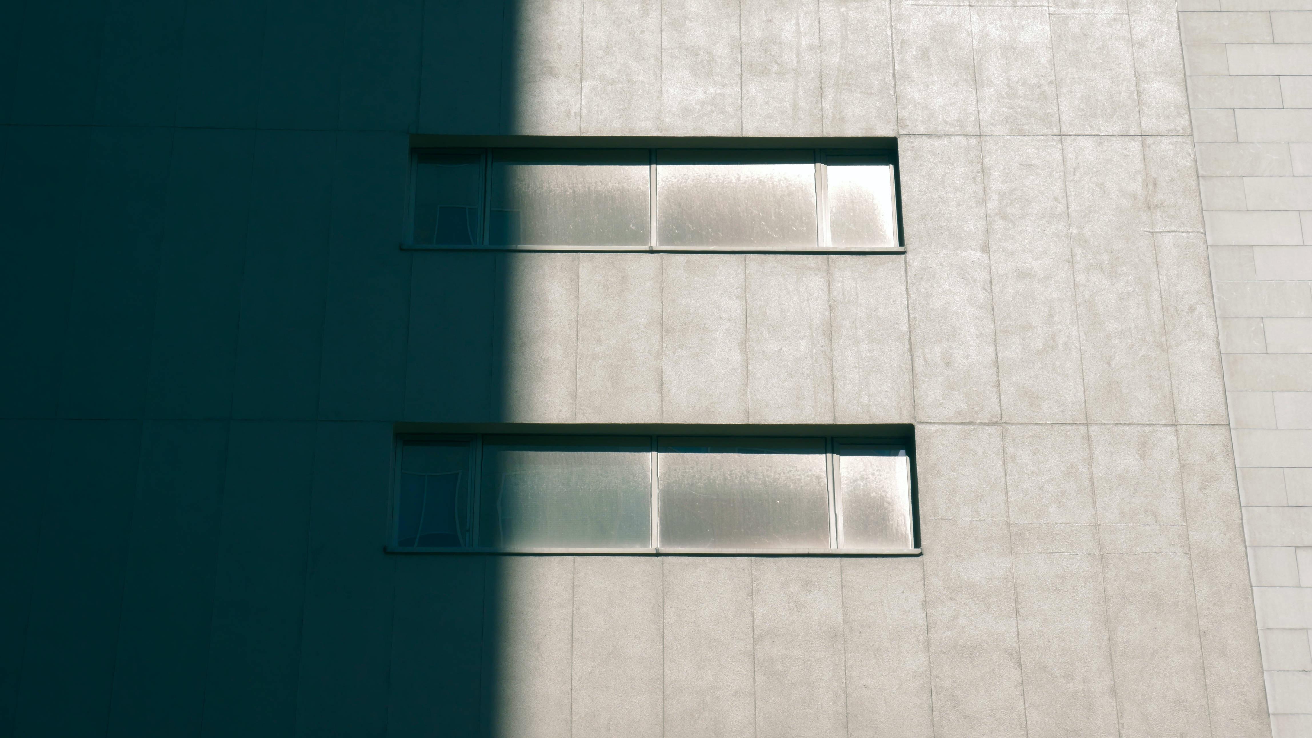 Concrete building with horizontal windows half in shadow