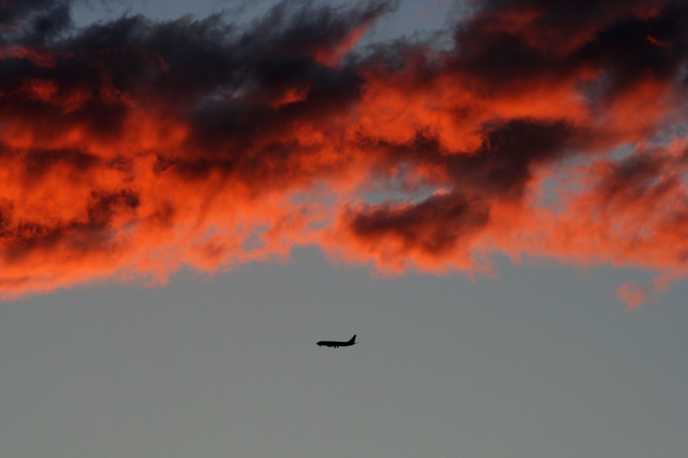 silhouette of plane on air under orange sky