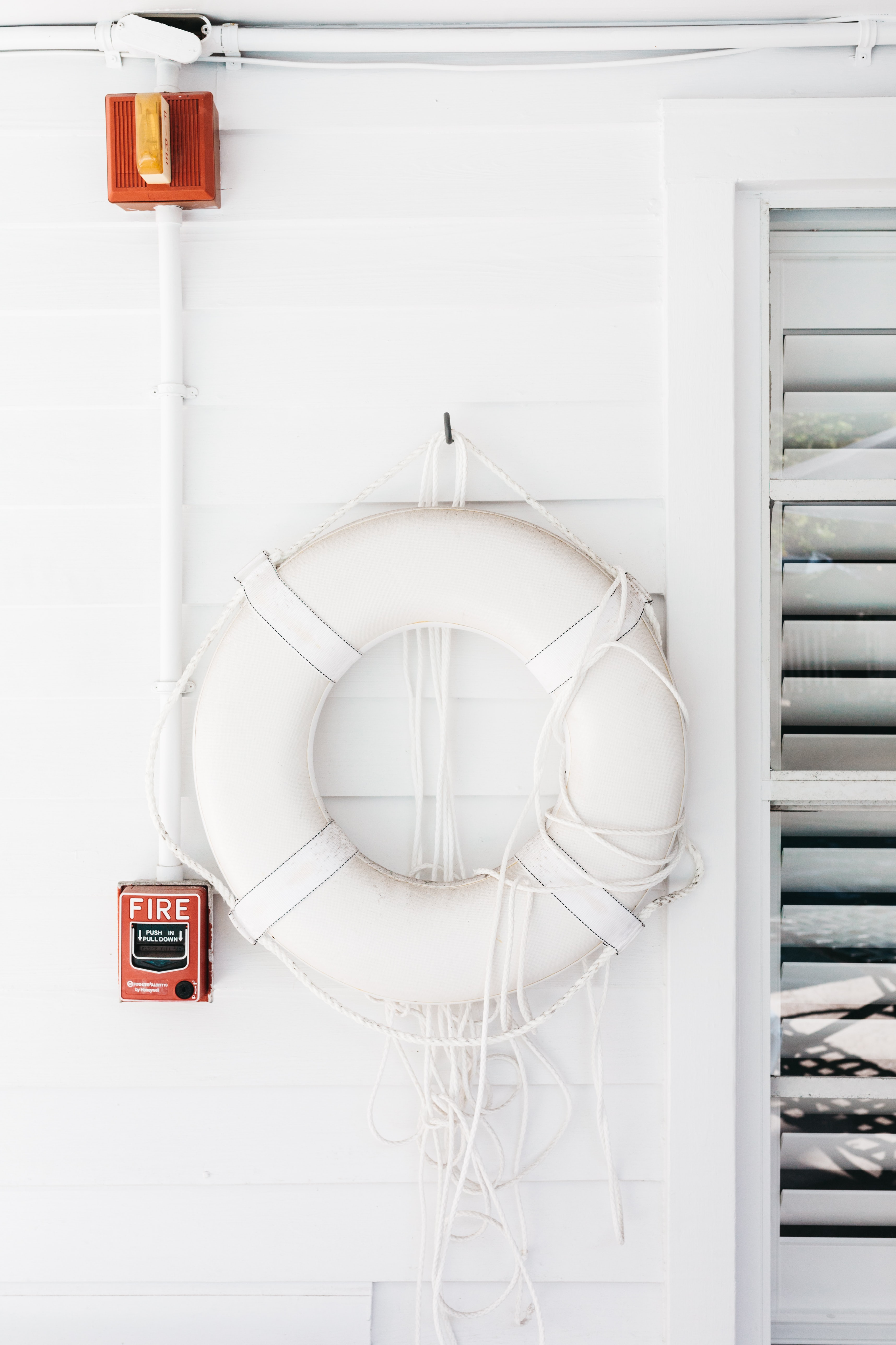 A white life belt on a white wooden wall next to a window