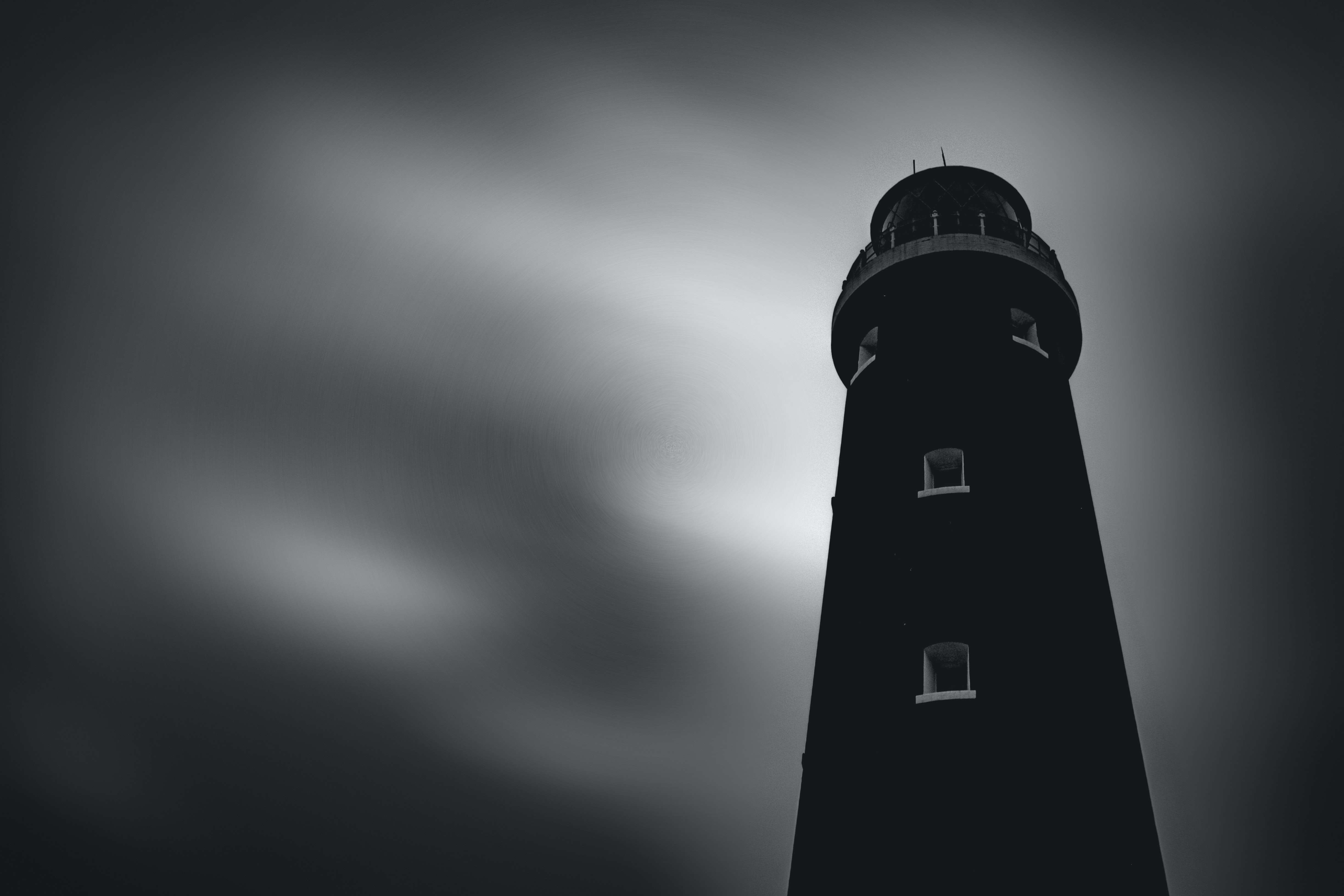 Black and white shot of traditional lighthouse against cloudy sky