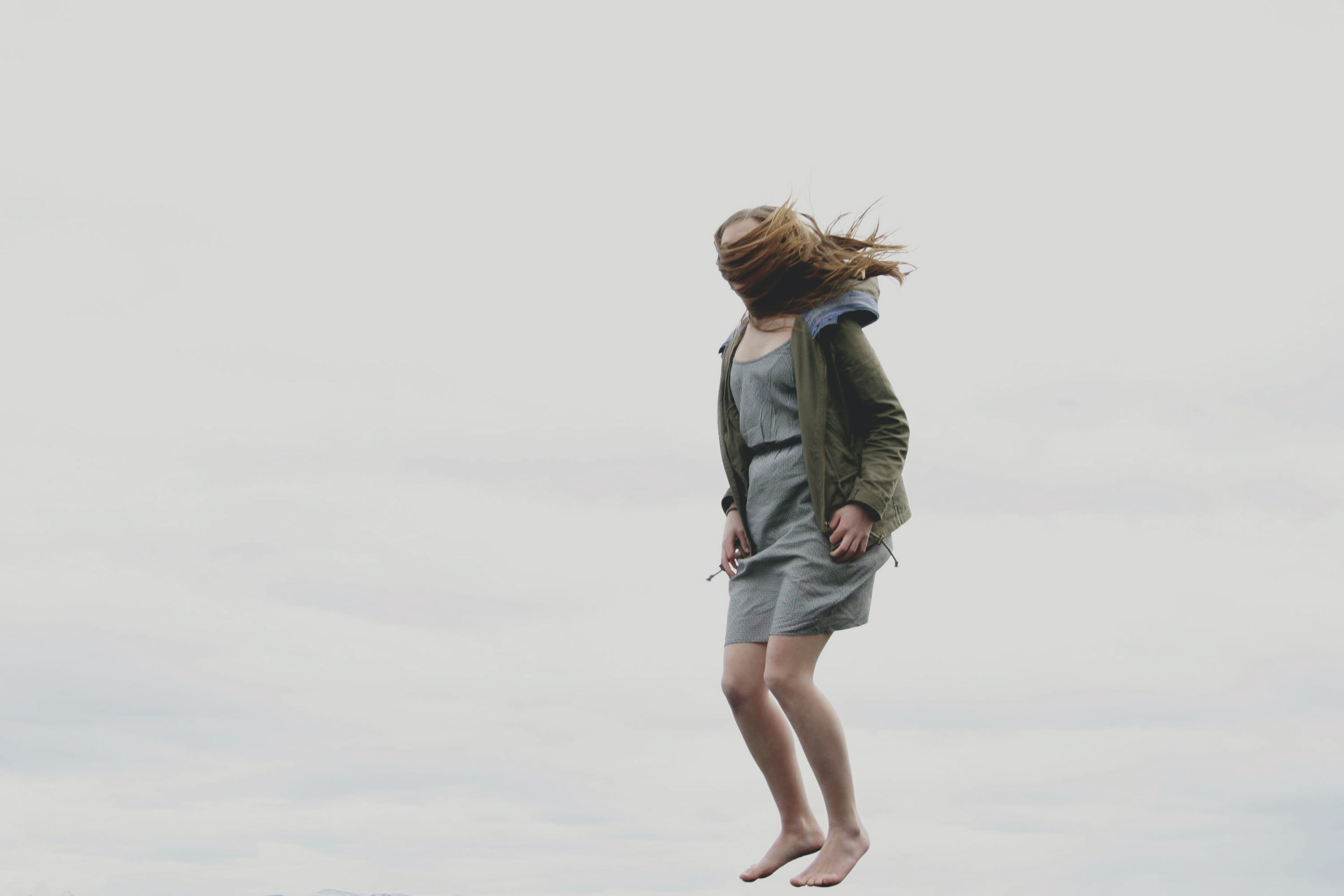 photography of woman covered with her hair while jumping