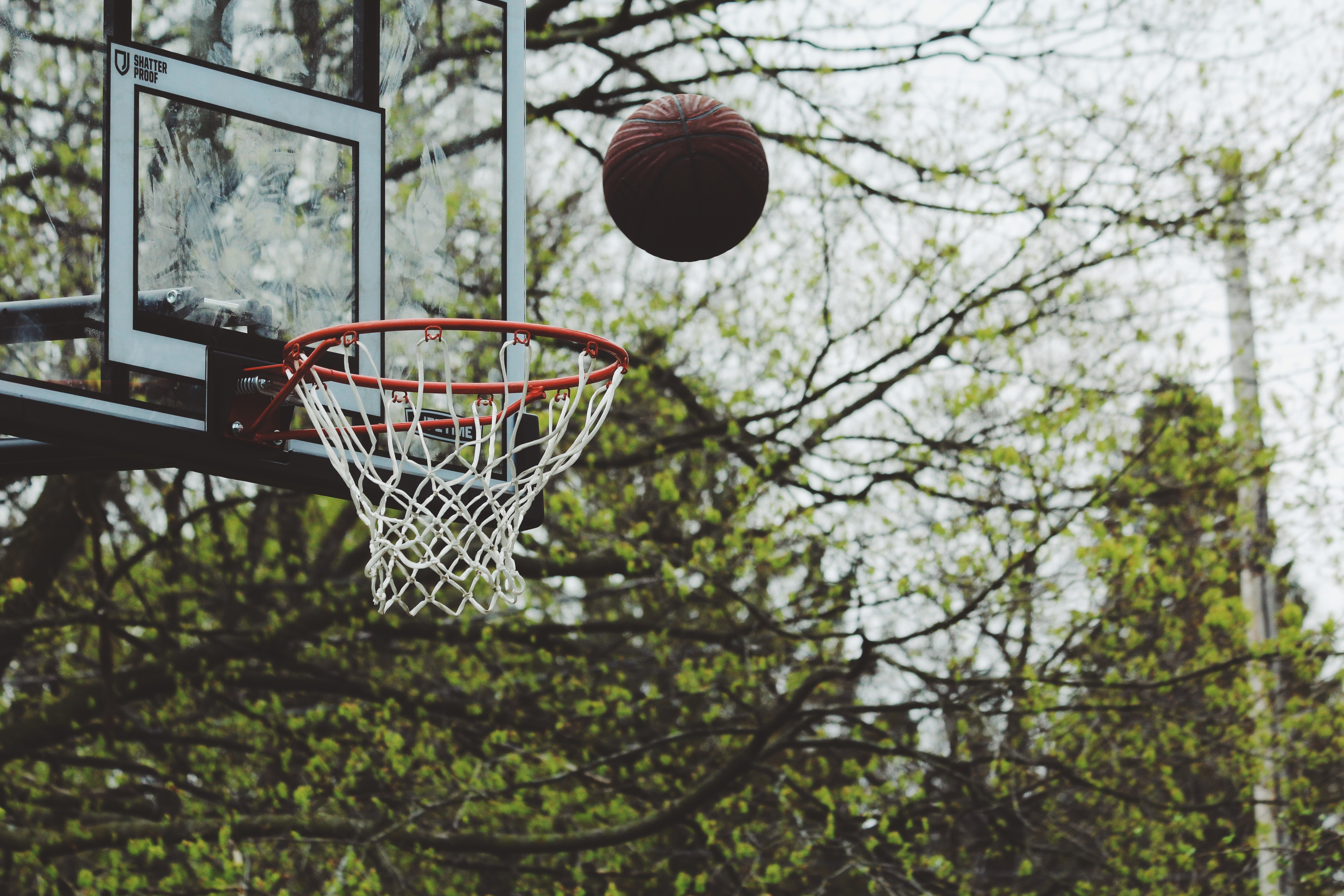 A basketball soaring towards the hoop on an outdoors court