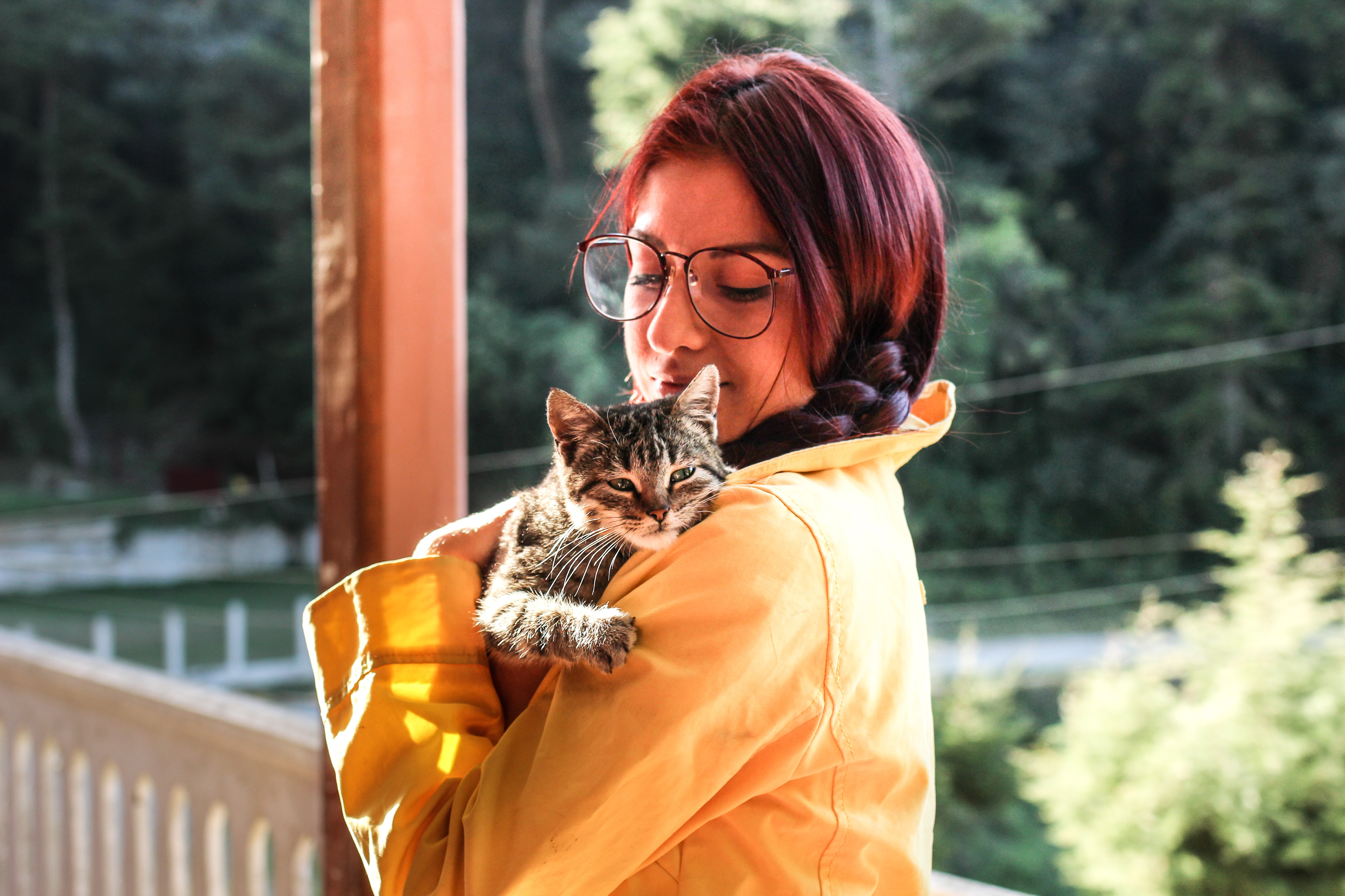A woman in a braid and large sunglasses holds a small cat on a porch