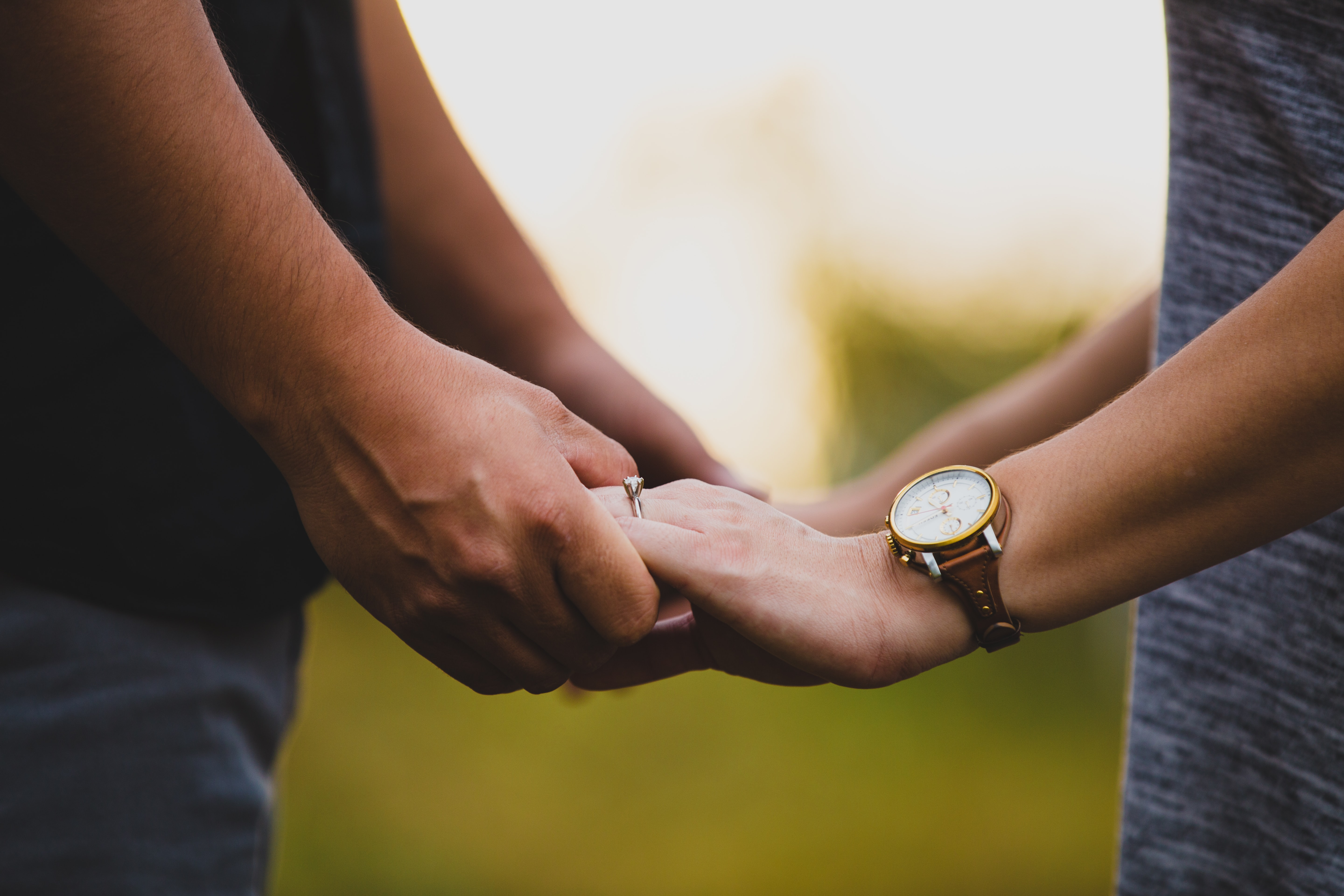 Close-up outdoors of man holding the hands of woman wearing a watch