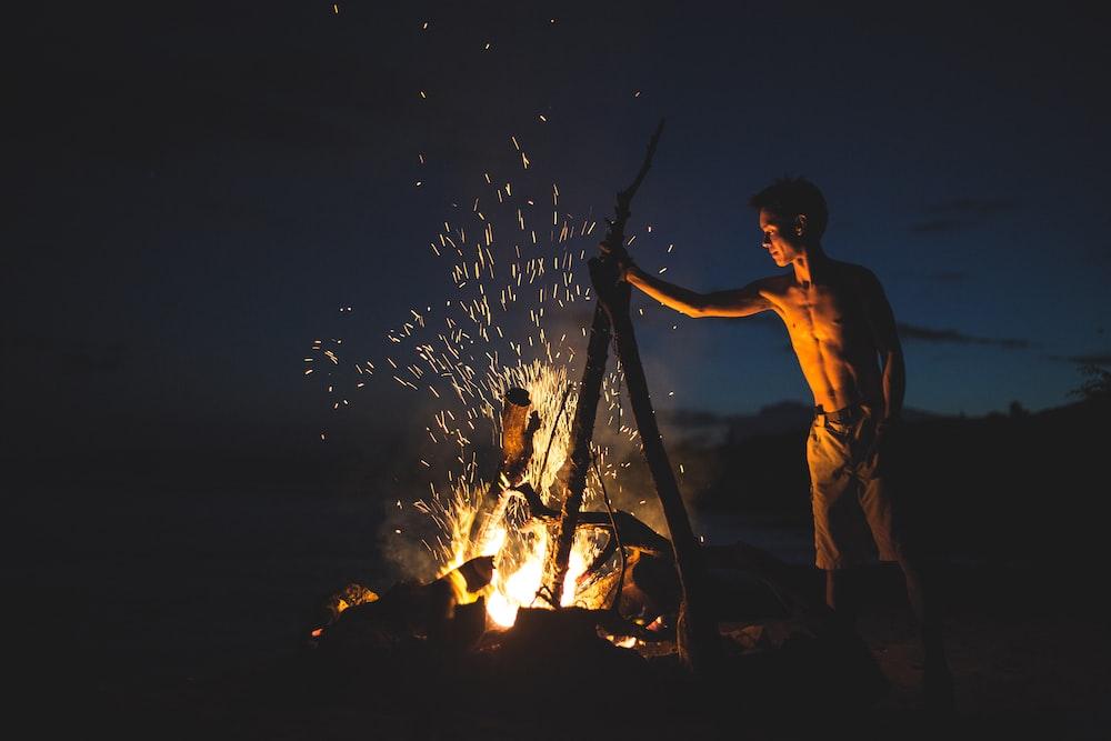 topless man lighting bonfire