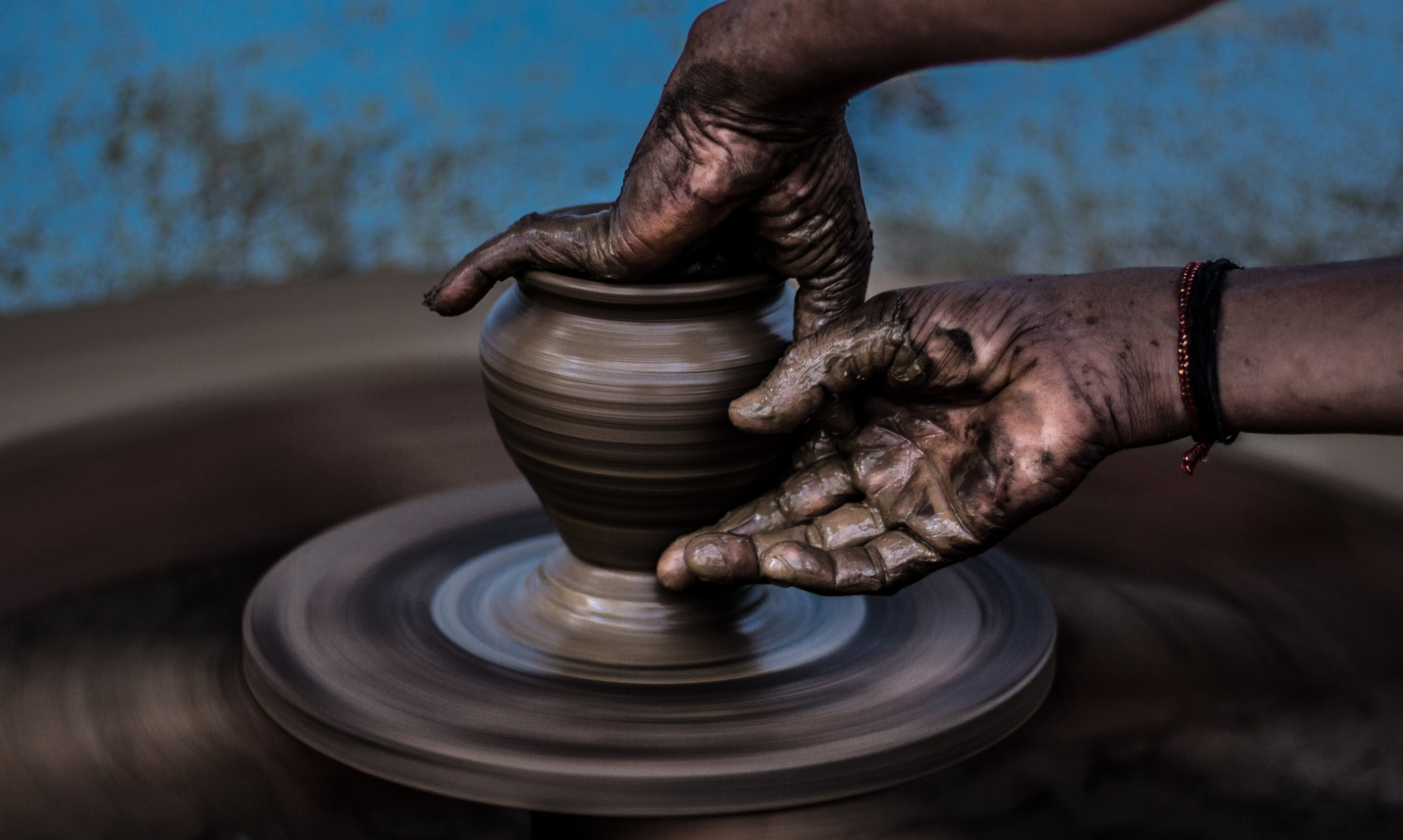 Hands create art on a pottery wheel