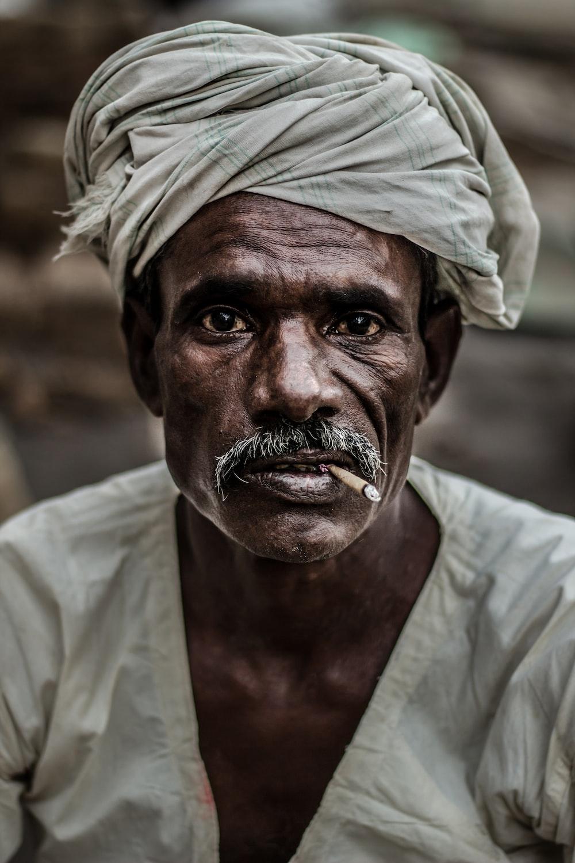 man wearing gray turban smoking cigarette in closeup photography