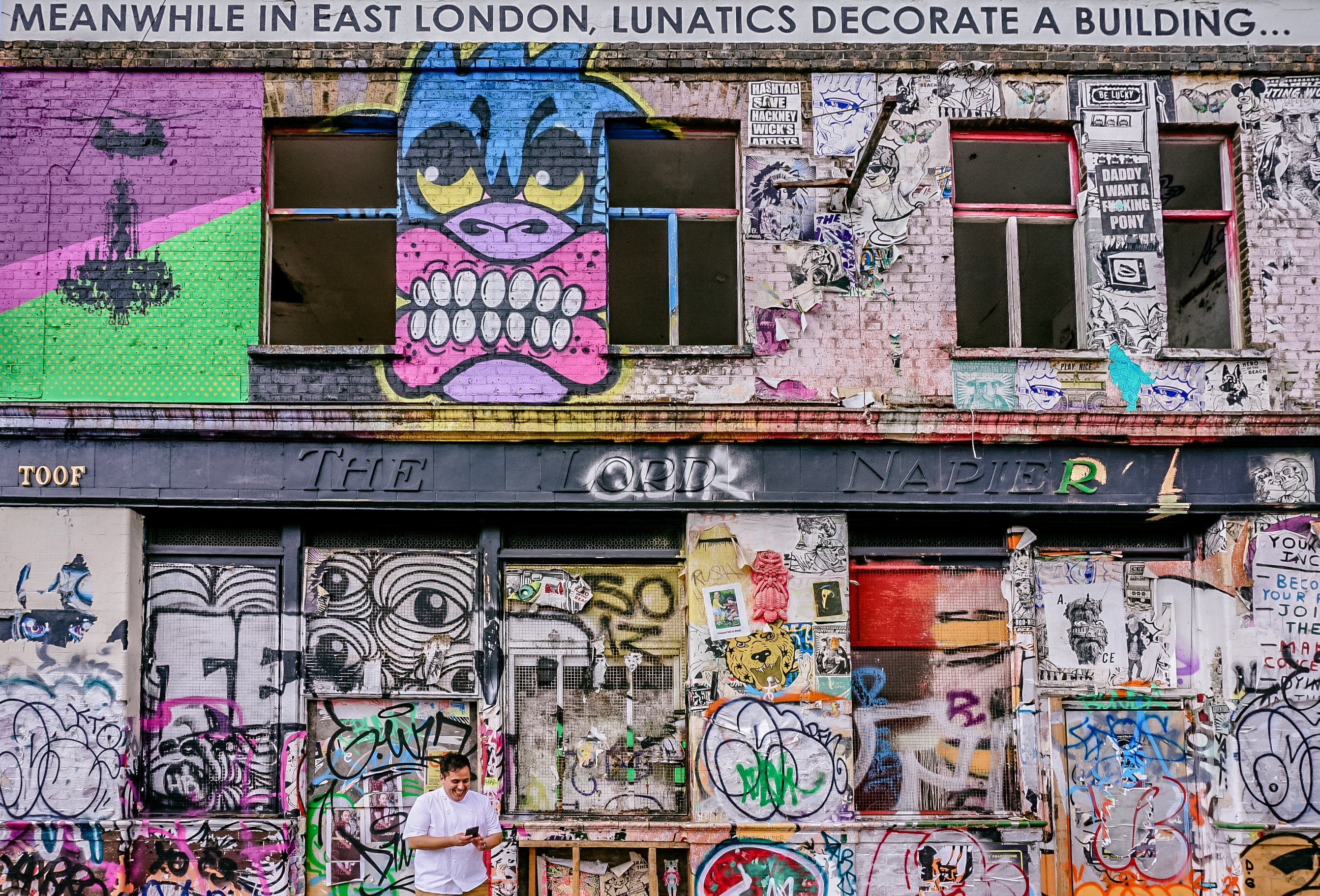 A dilapidated building facade covered in graffiti in Hackney Wick, London