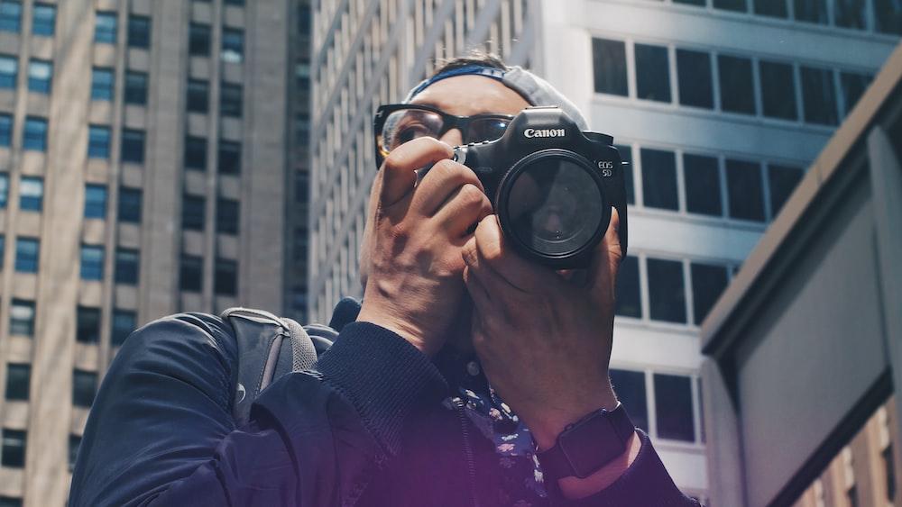 man holding Canon DSLR camera