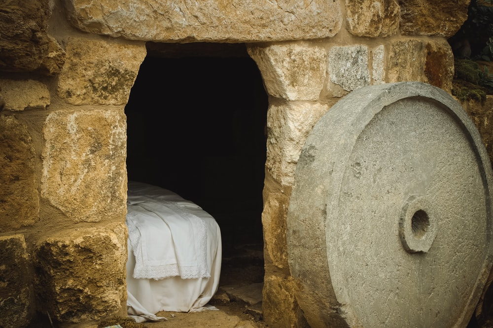 A cement wheel next to a brick building with a sheeted bed inside.
