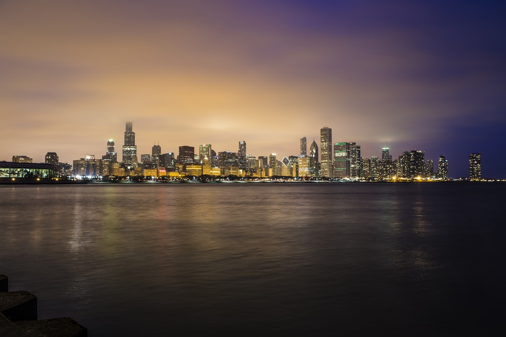 city skyline near body of water during golden hour
