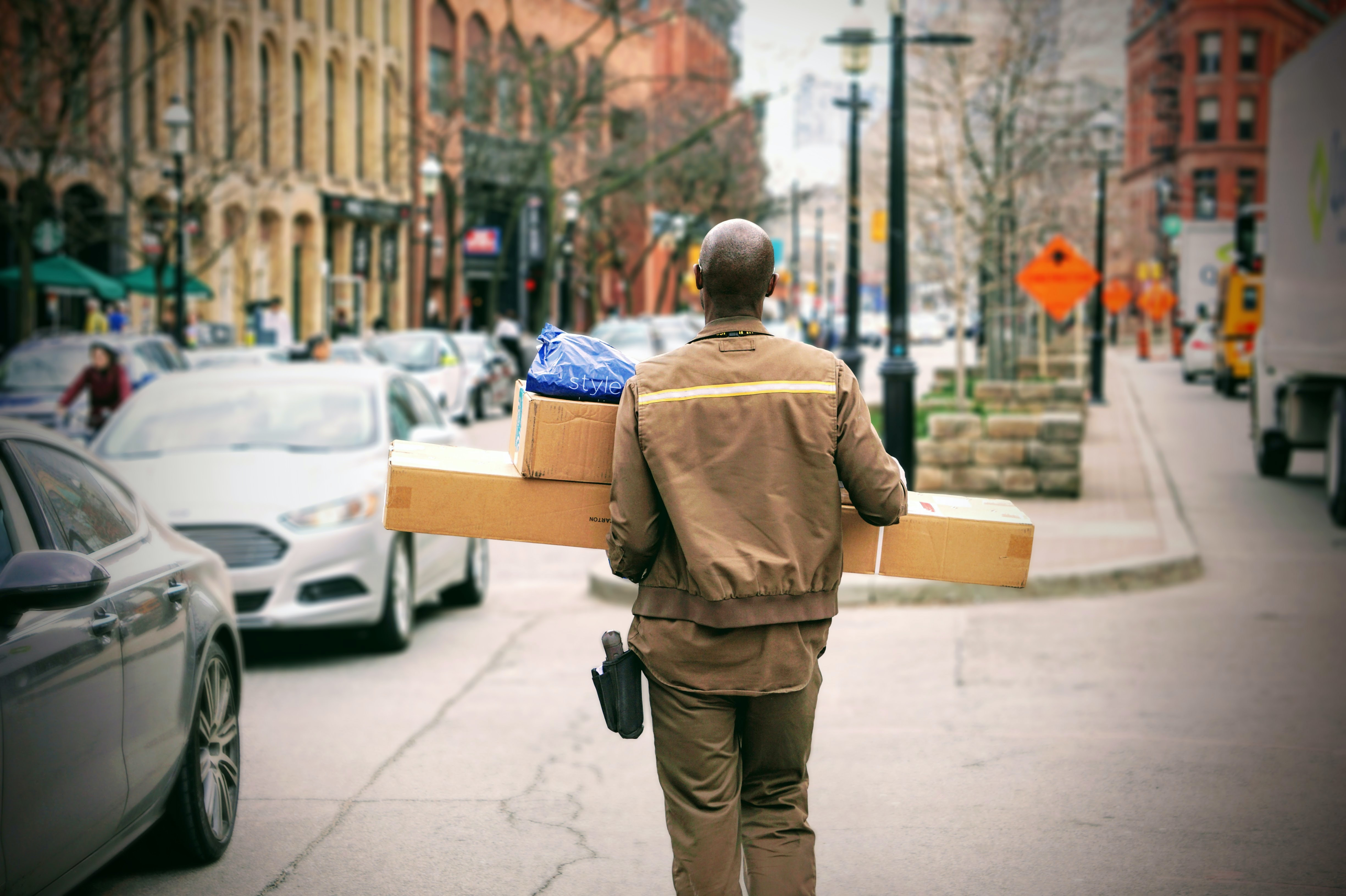 A bald man in uniform is carrying parcels next to a busy street in St. Lawrence Market.