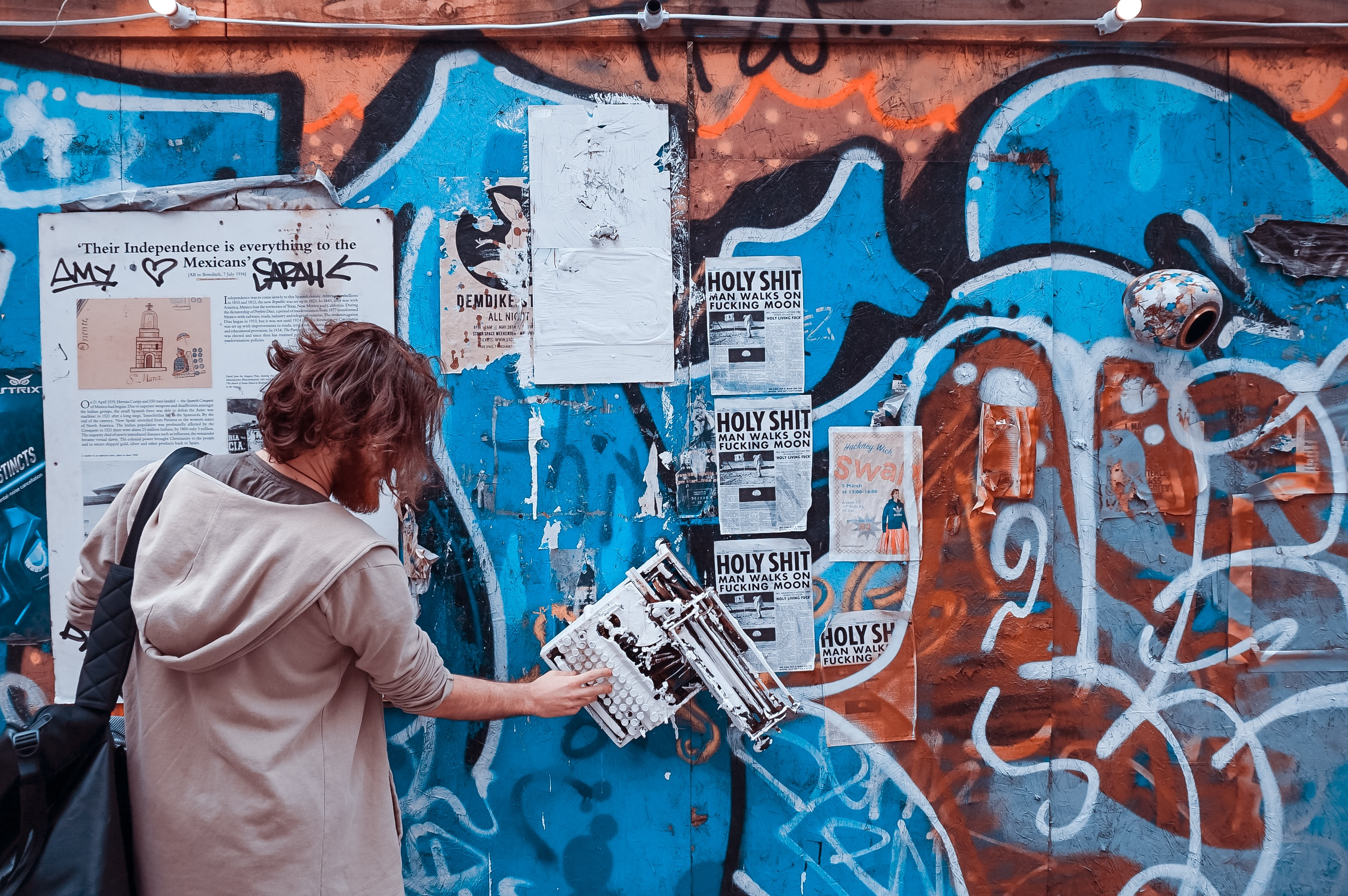 A man putting up posters over a wall covered in graffiti.