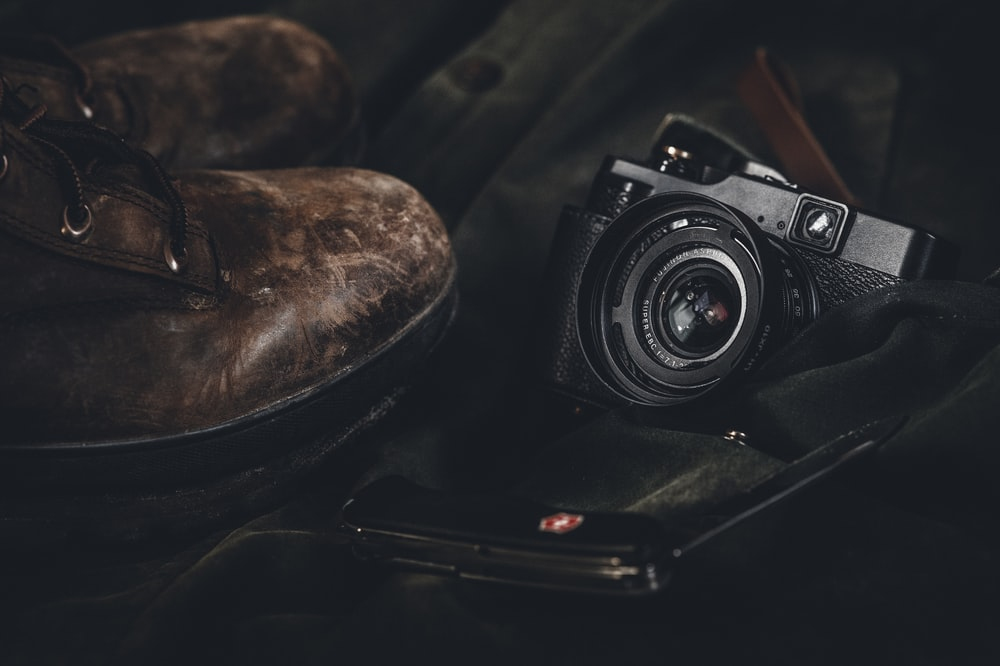 photo of a black point-and-shoot camera and pair of brown leather boots