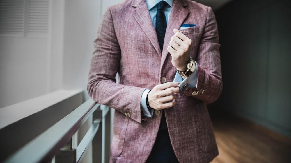 man in maroon suit jacket beside window with railings