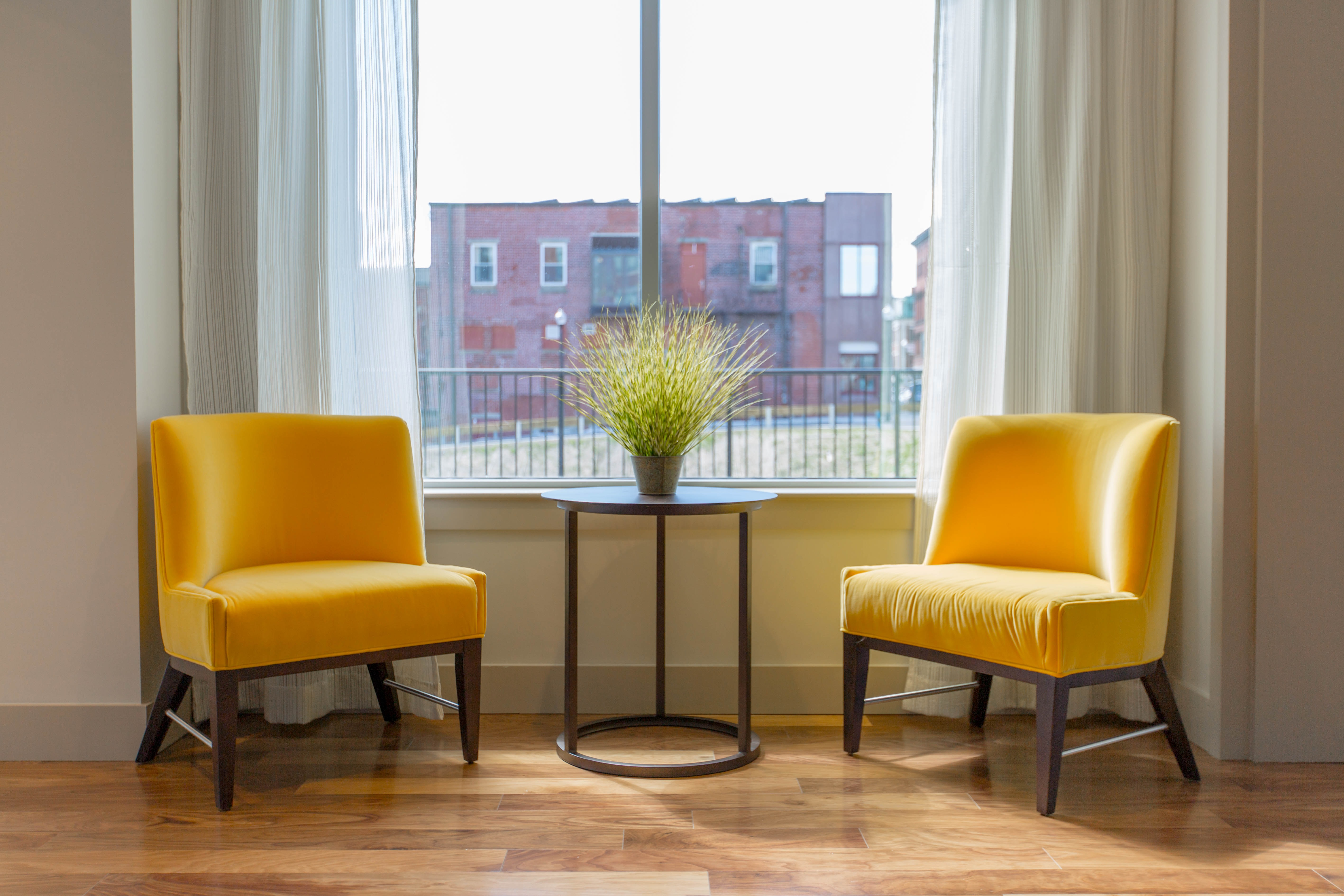 Two Yellow Chairs Flank Table With Plant In Front Of Window Looking Out At  Red Building