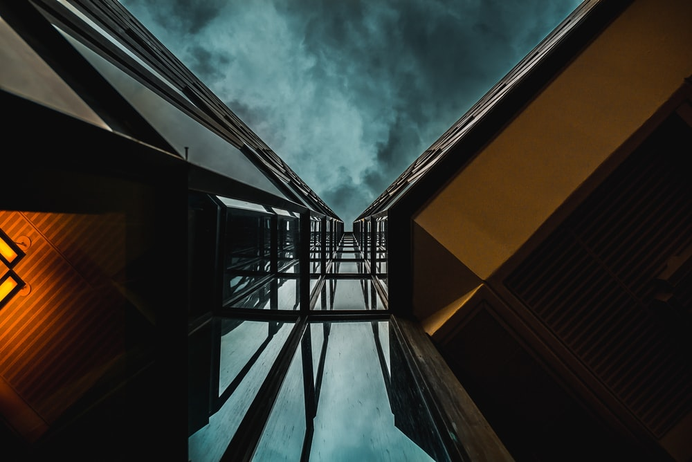 low angle photography of high-rise building under blue clouds