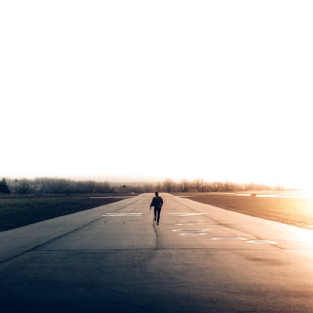 A man running down the airstrip at Burlington Executive Airpark Airport