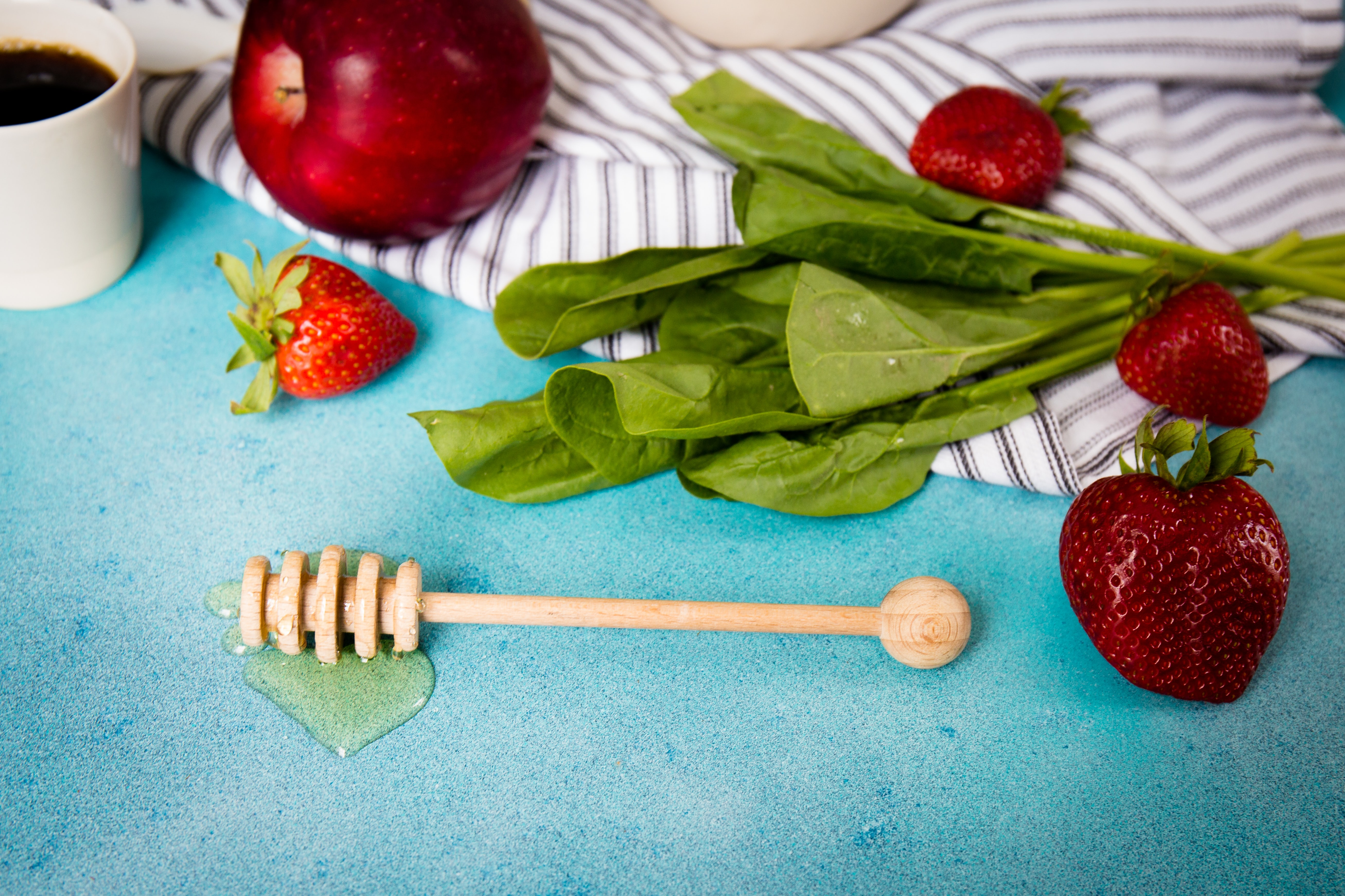Wooden honey dipper stirring rod on a blue surface next to leaves, apples, strawberries and a mug of coffee