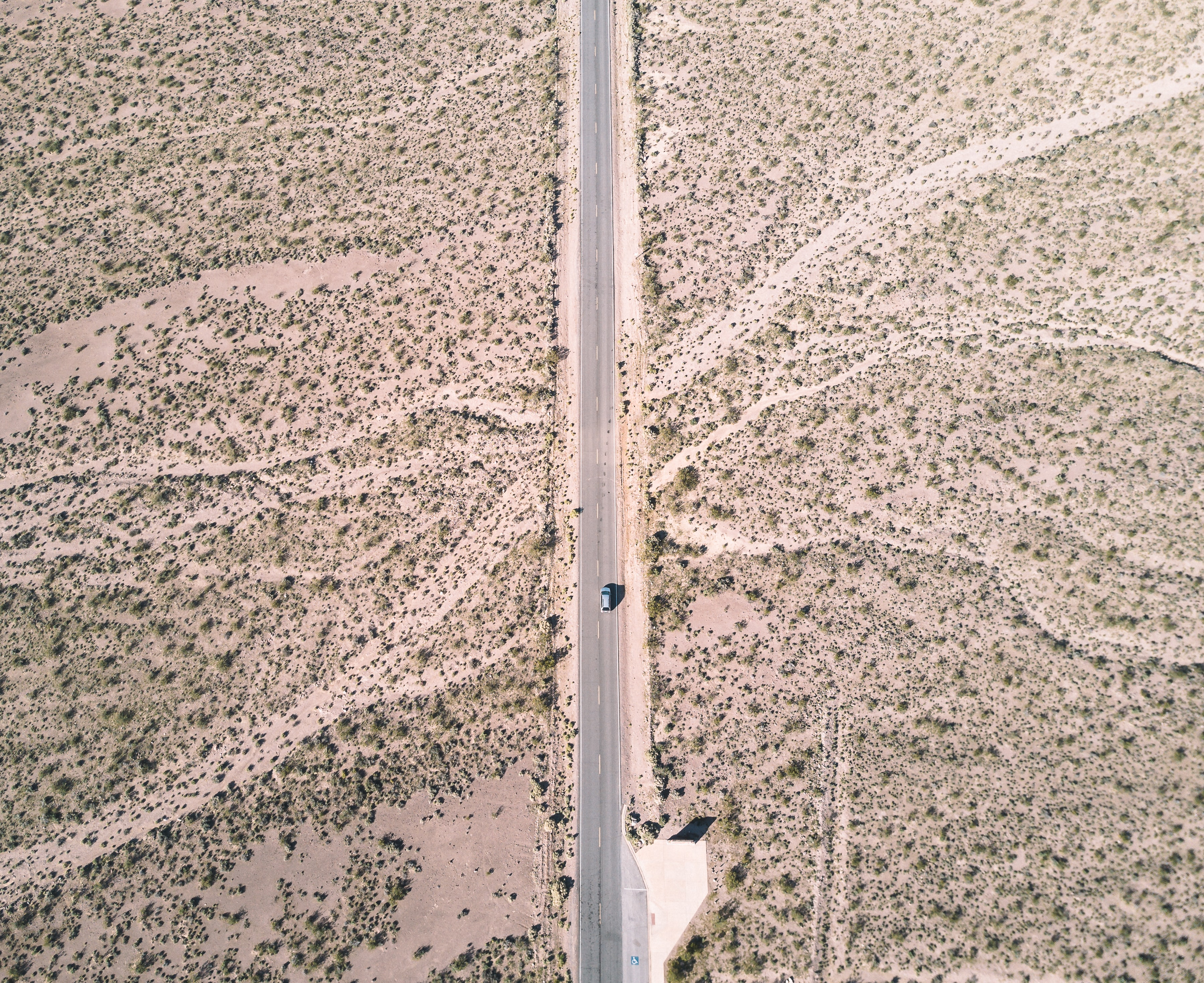 Top down view of a single blue car driving down a highway cutting through a desert in Nevada.