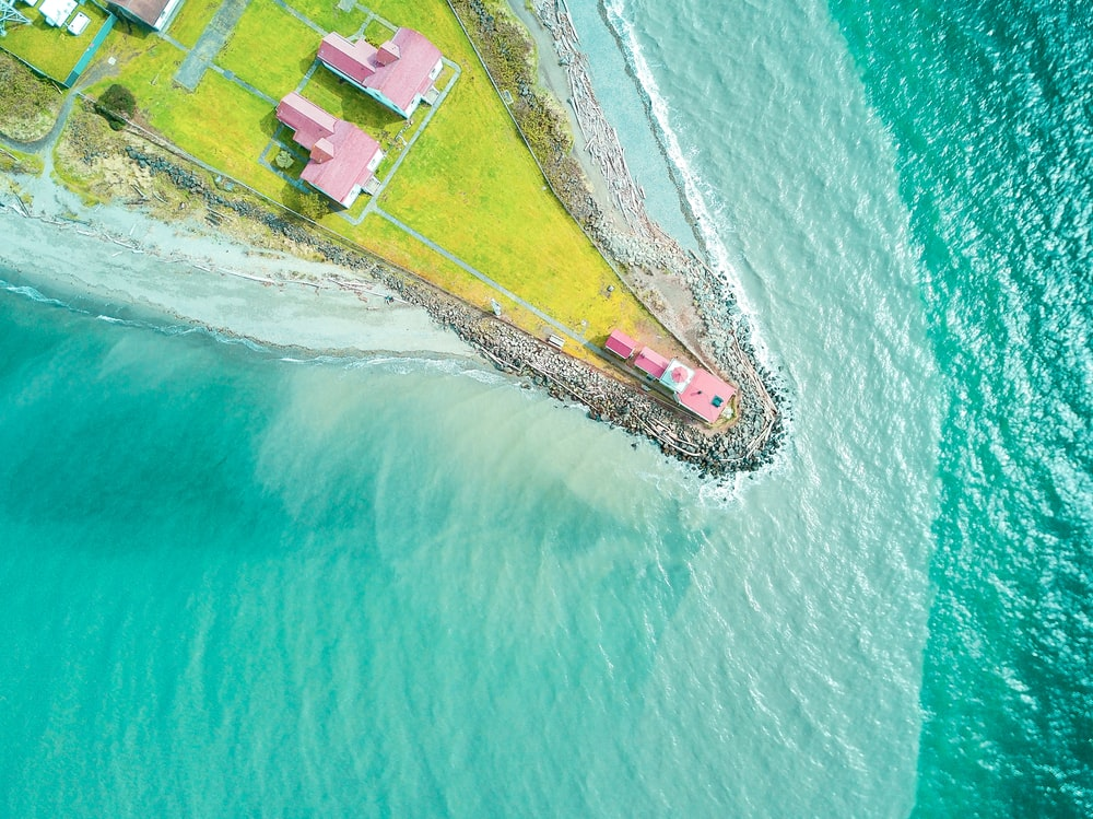 aerial photography of pink house at the edge of land near body of water