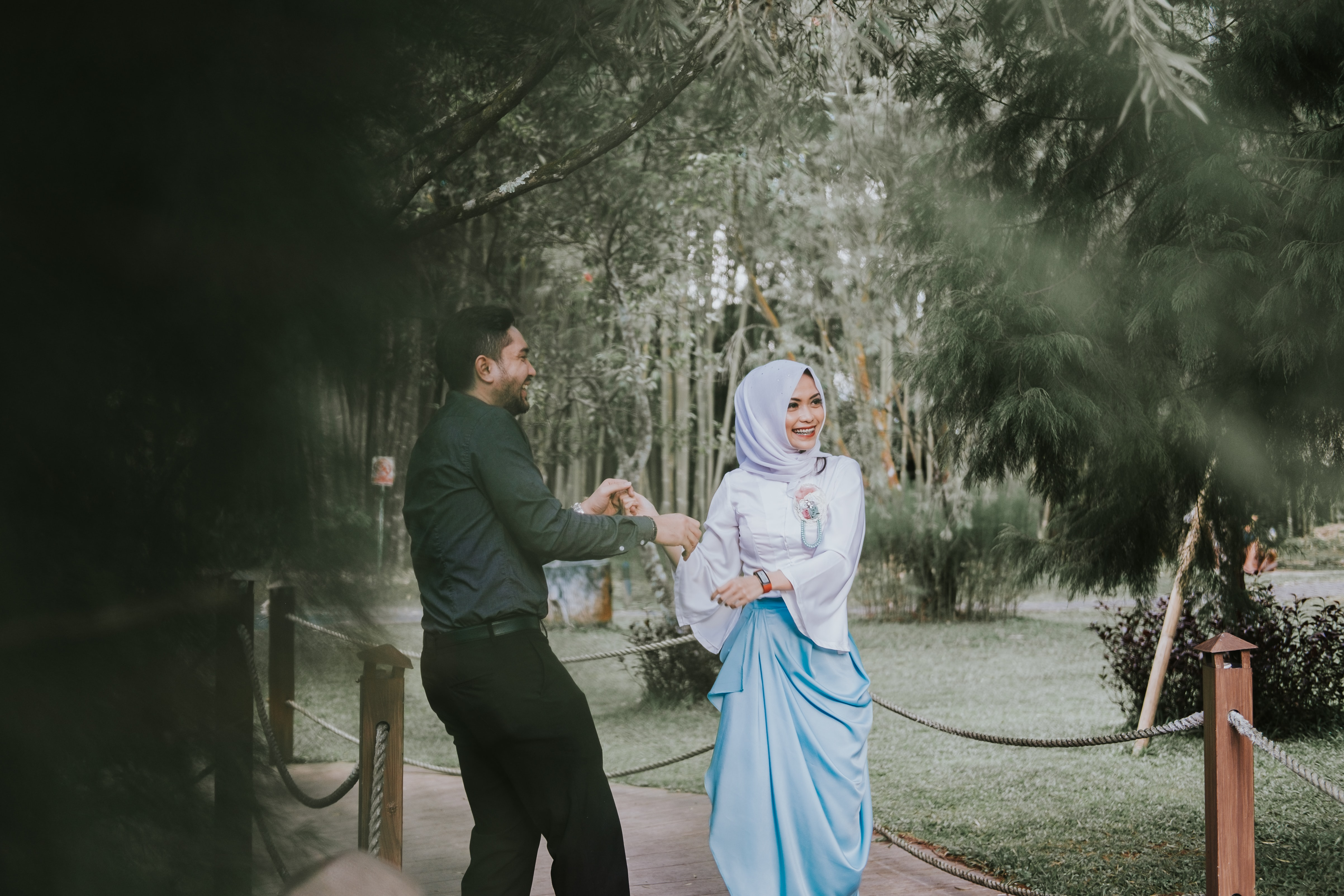 A man and woman in hijab dance on a path outside The Hill Hotel & Resort Sibolangit