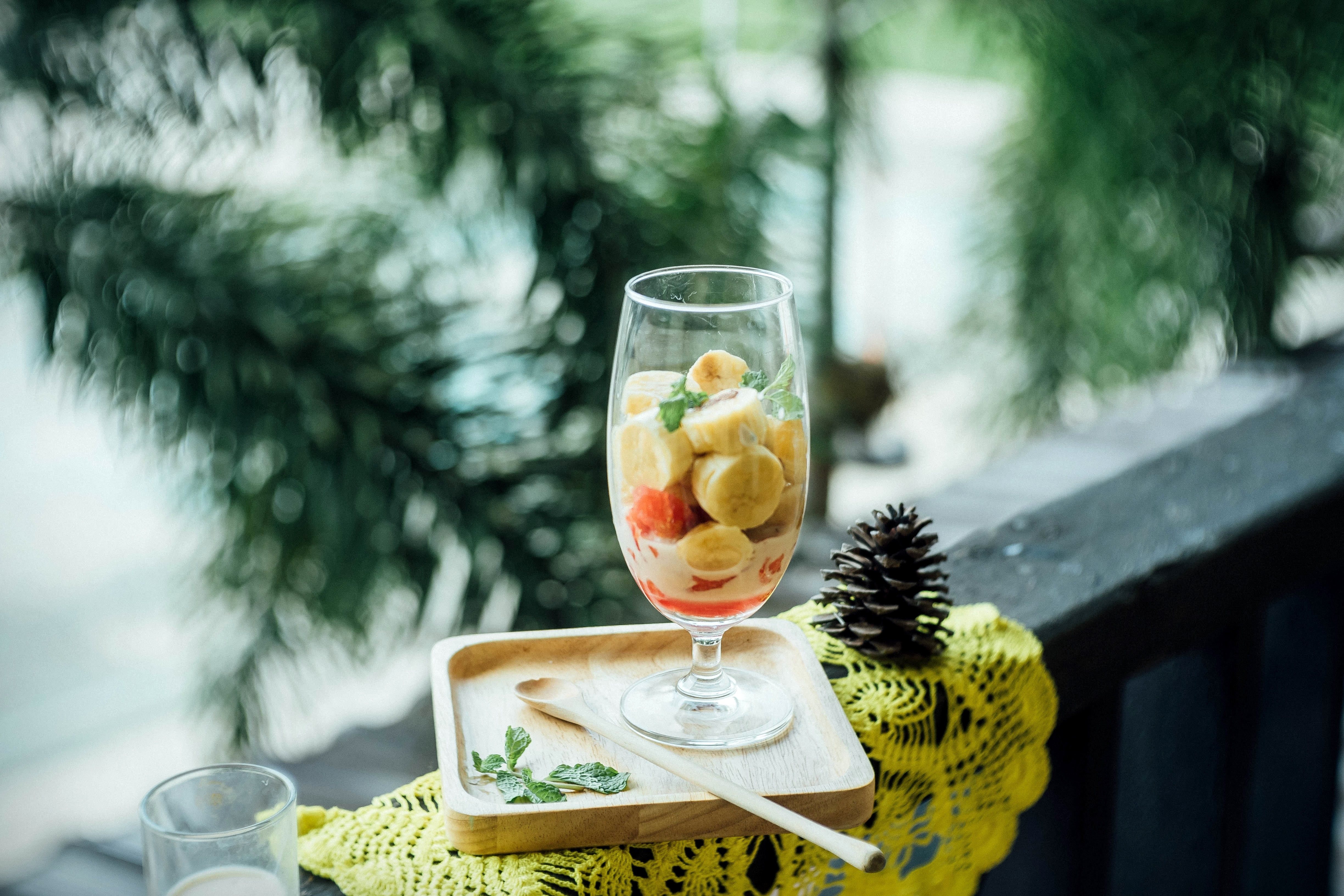 clear footed glass filled with fruits on brown wooden tray