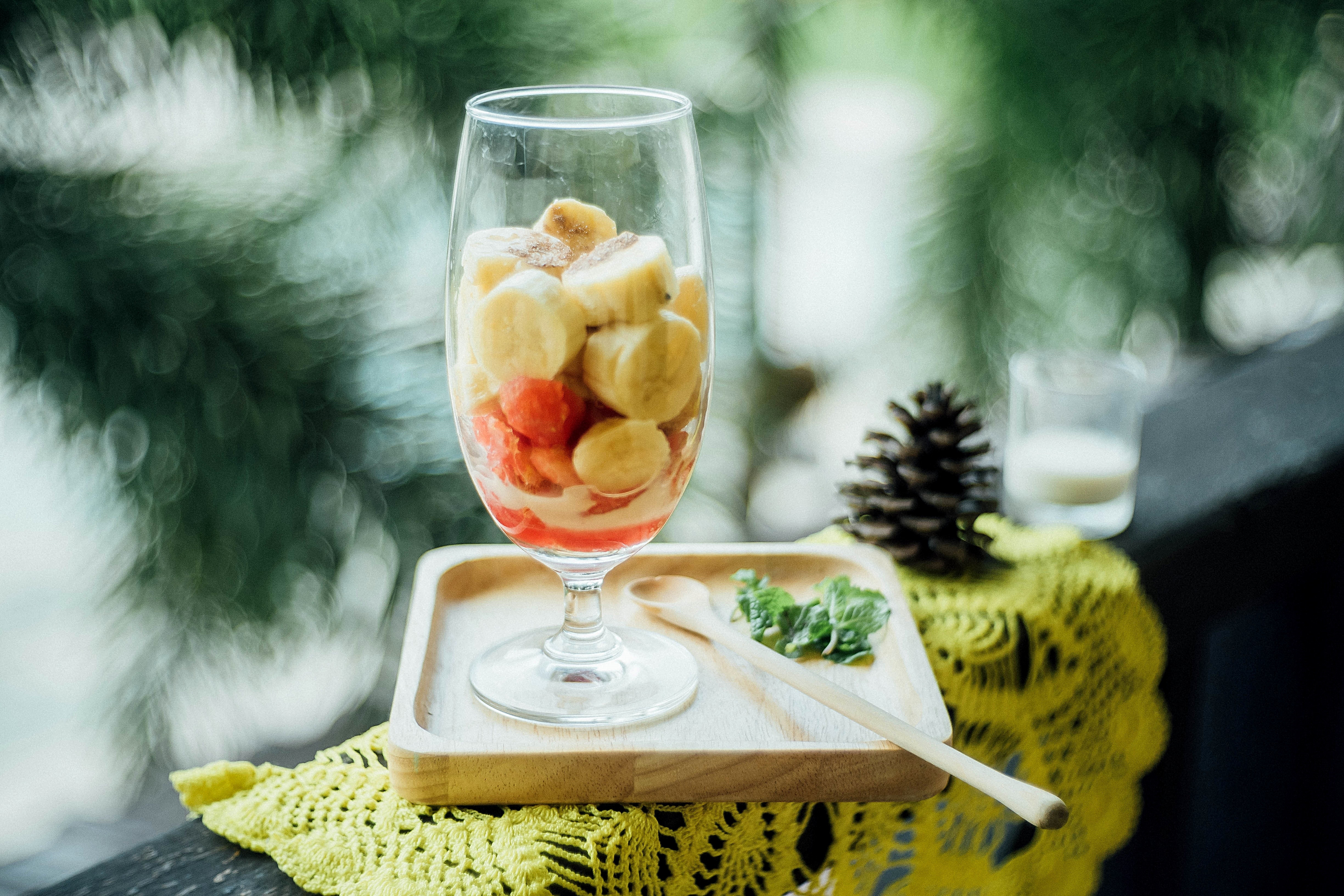 A glass of chopped bananas and strawberries beside a long wooden spoon and mint on a wood coaster on top of a yellow doily next to a pinecone and a glass of milk