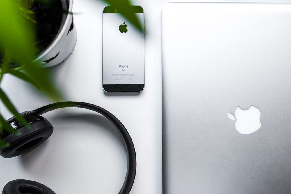 space gray iPhone SE beside headphones and silver MacBook