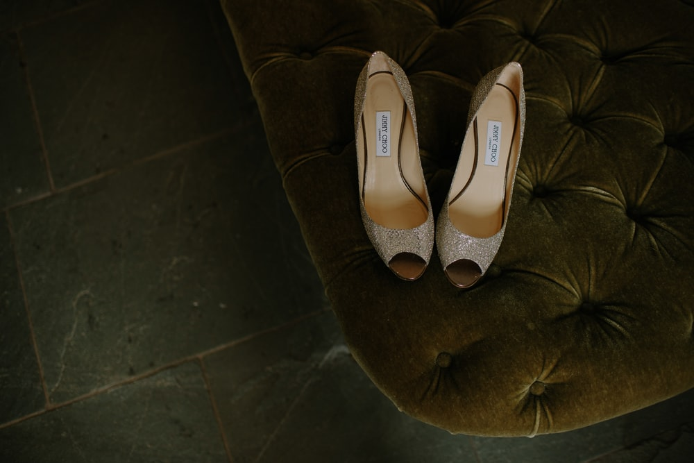 Pair Of Brown Gray Leather Open Toe Heeled Shoes On Tufted Mattress