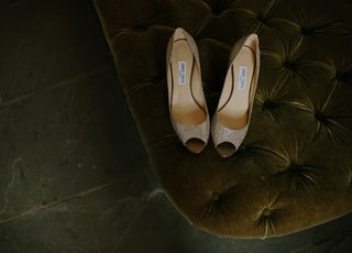 pair of brown gray leather open-toe heeled shoes on tufted mattress