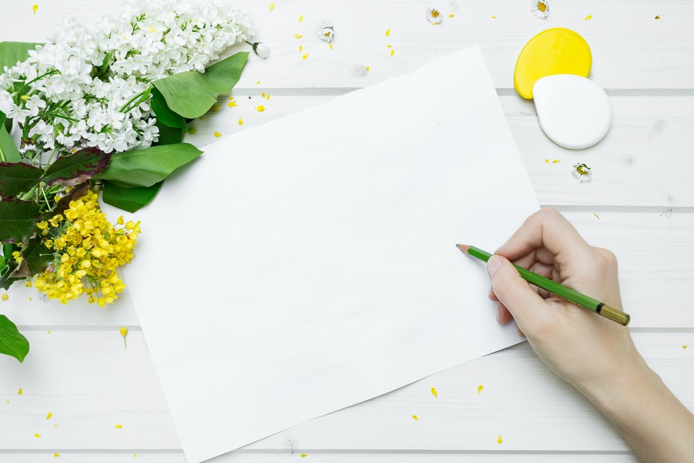 person about to write on white printer paperr