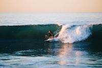 man surfing on ocean wave during daytime