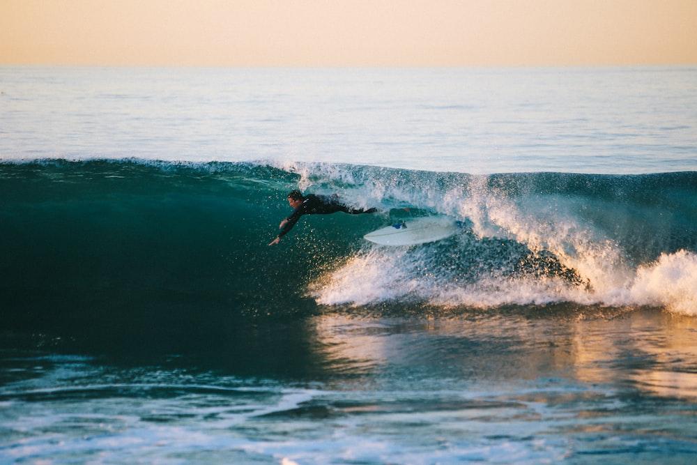 man surfing under wave