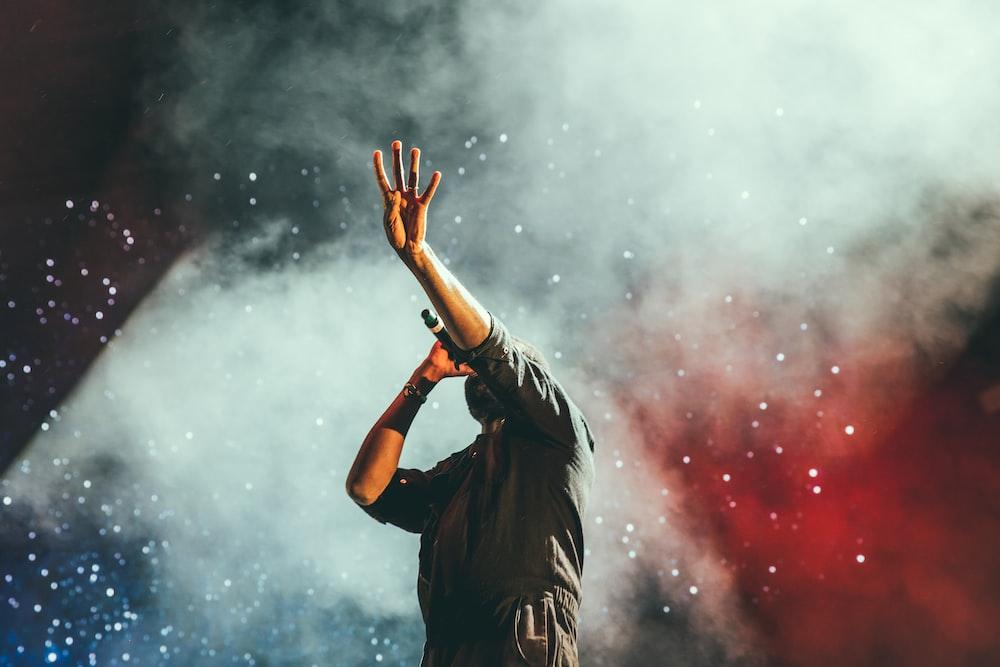 man in gray quarter-sleeved shirt singing