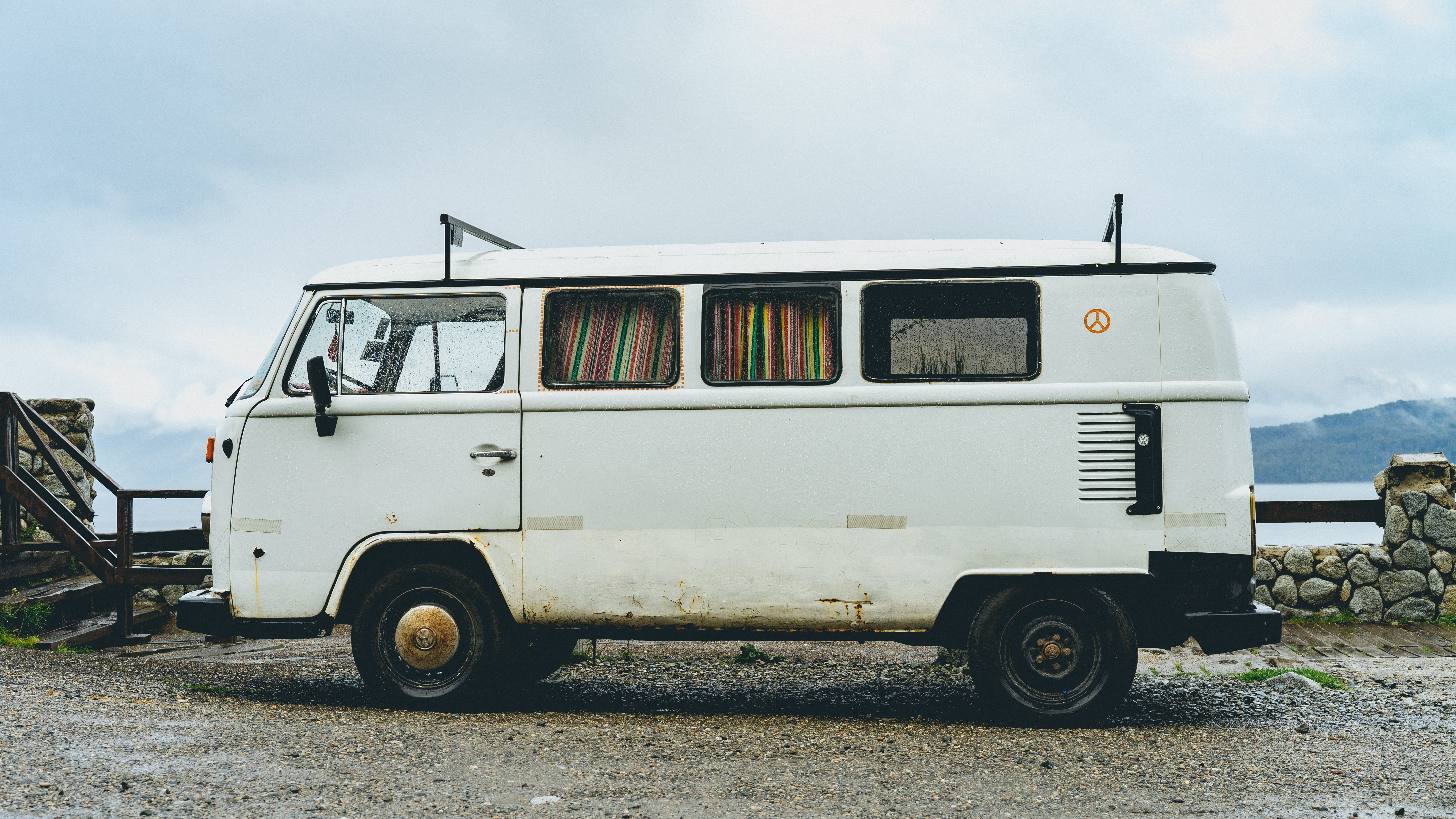 A white Volkswagen bus parked on a gravel surface by a lake