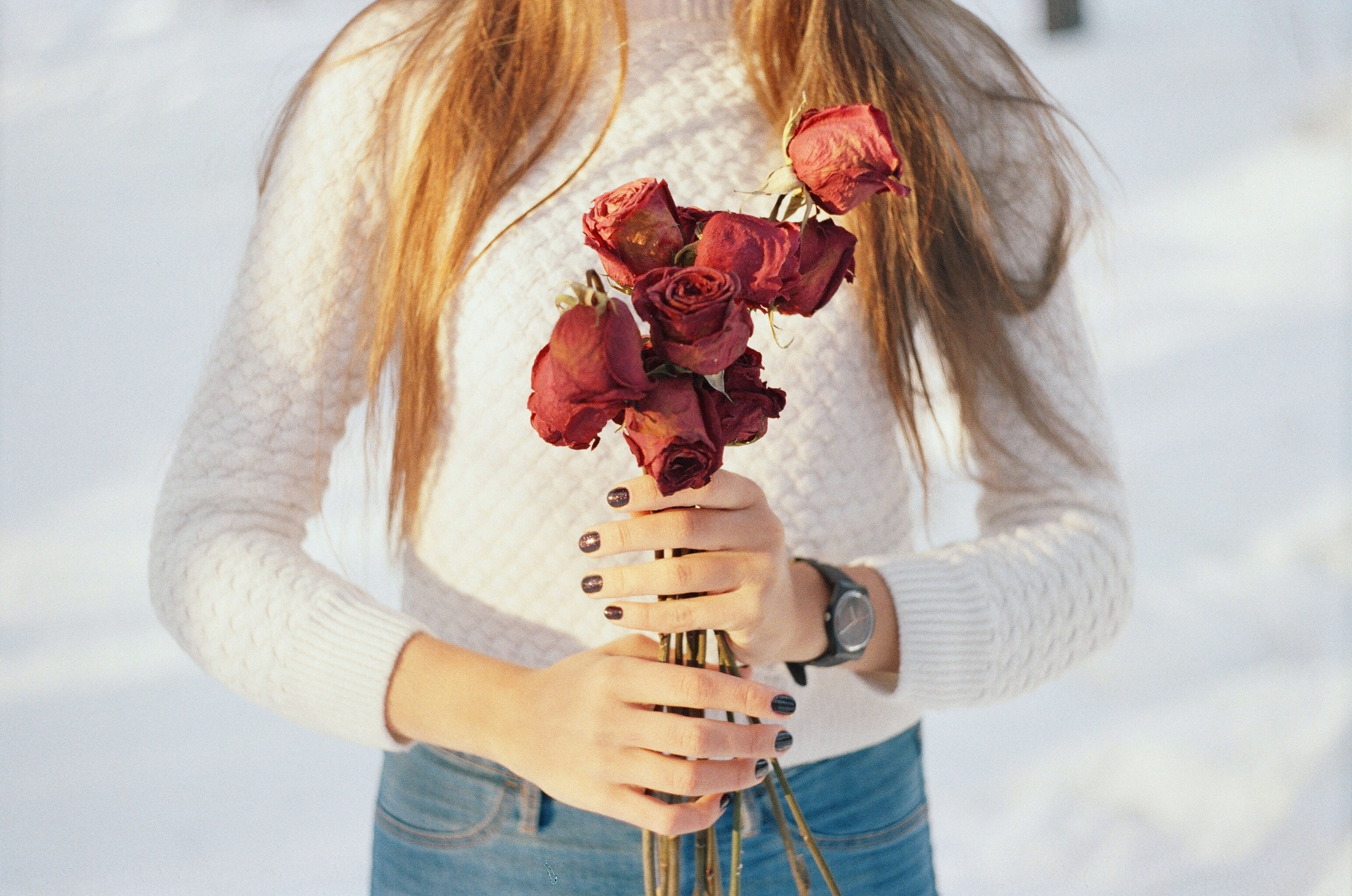 Low Shot of woman holding a bouquet of dried and wilted red roses