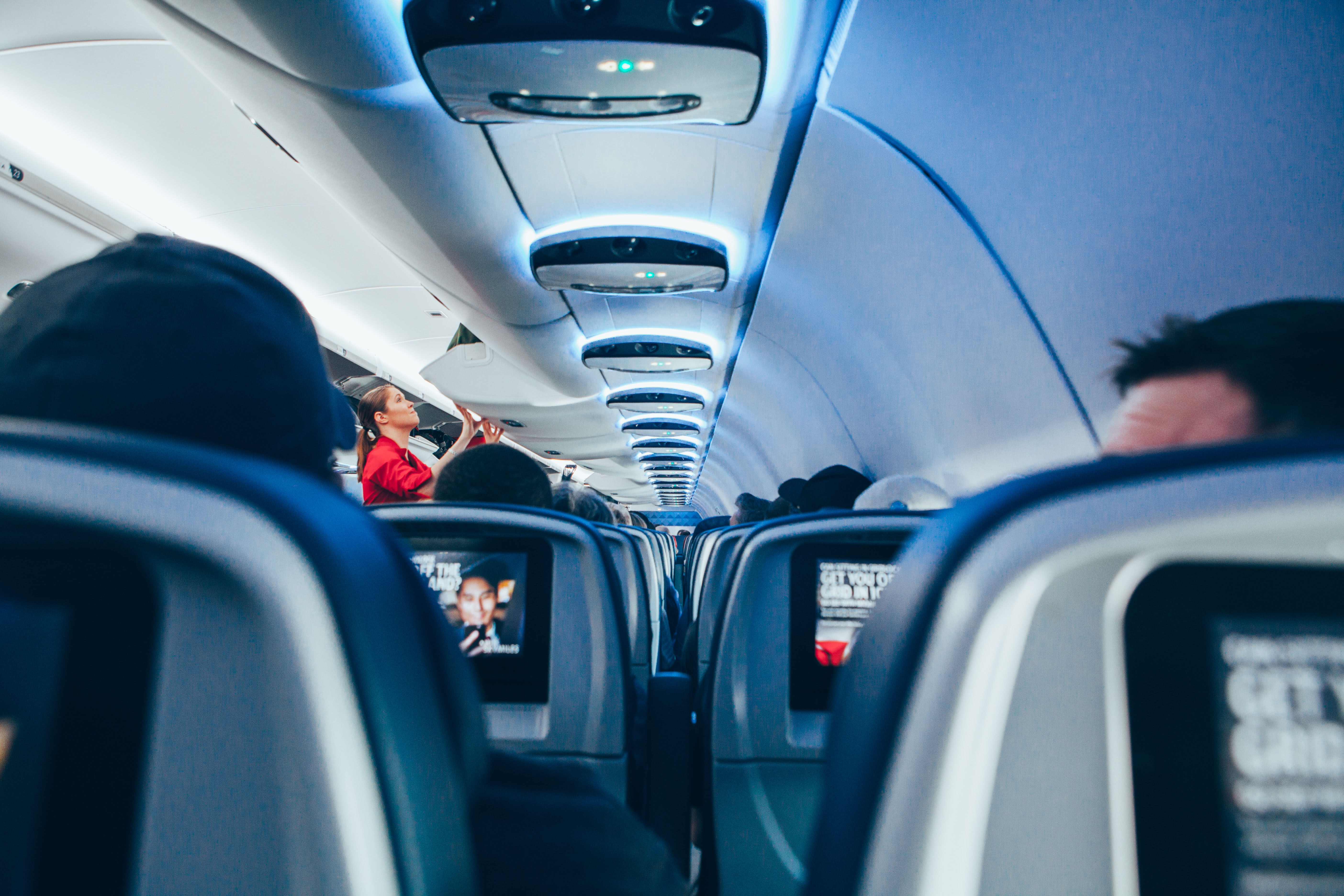 View from the back of a plane on the rows of seats stretching to its nose