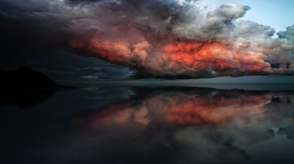 body of water under red and white clouds