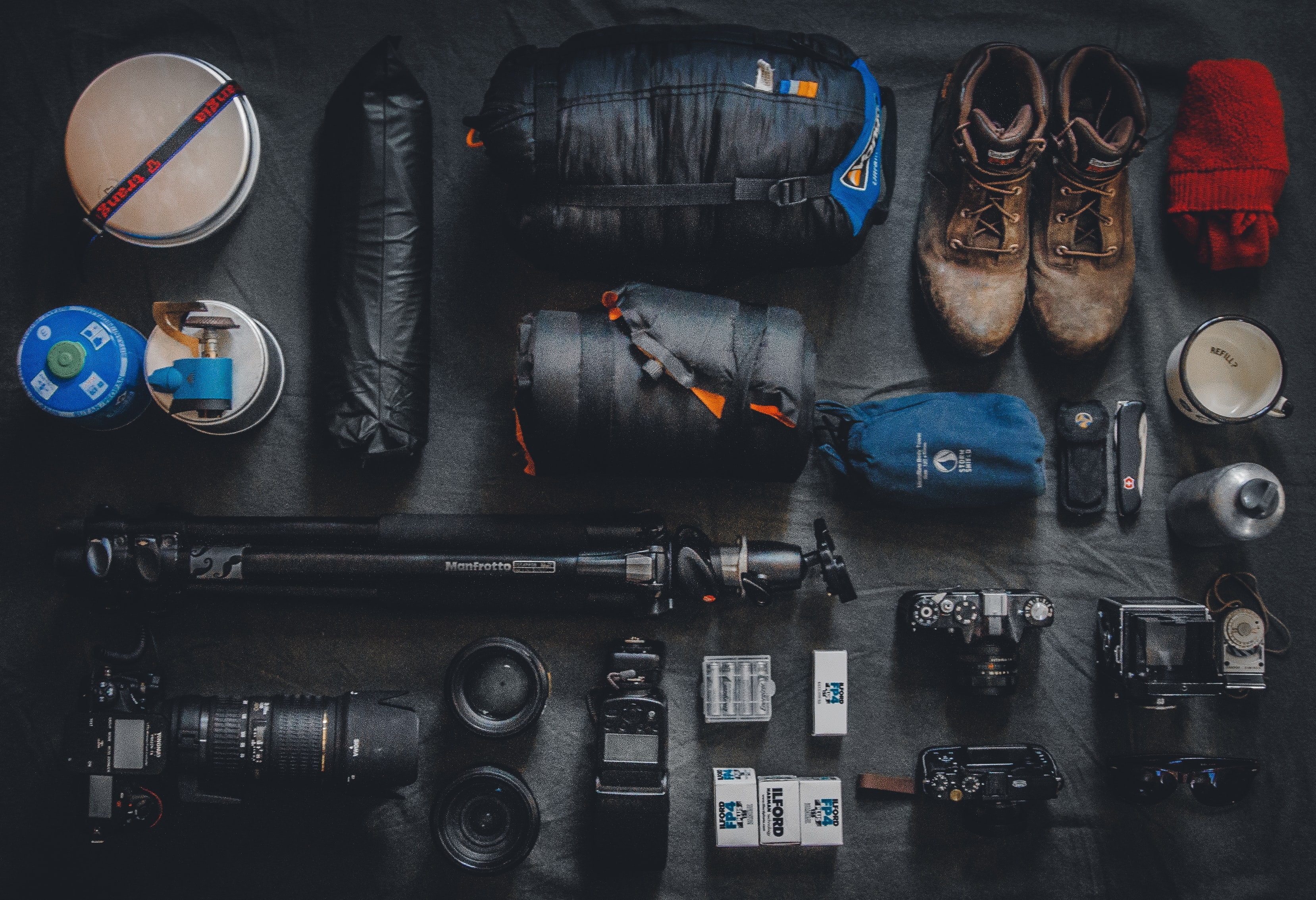 Neatly arranged boots and photography equipment including camera, lens, tripod, sleeping bag, and mug