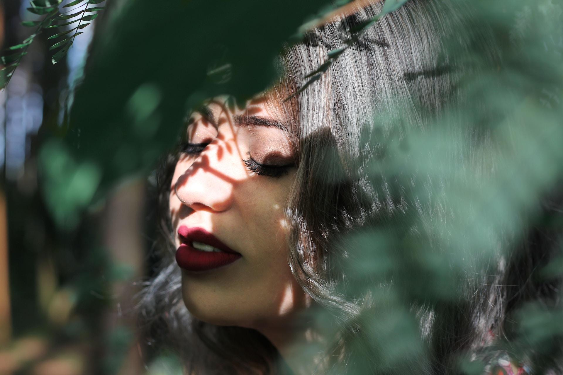 woman closing eye near leaf
