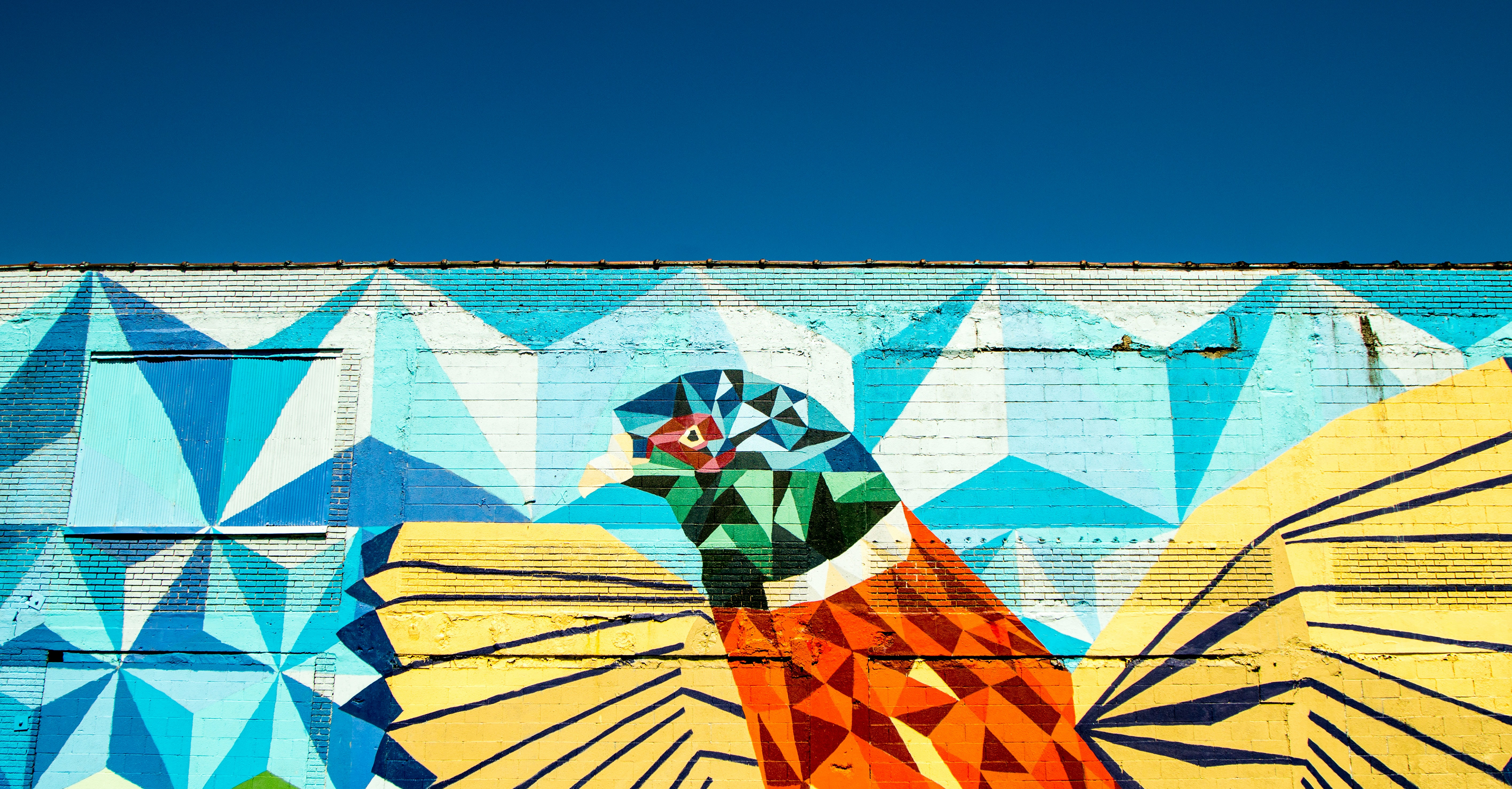 A colorful geometric graffiti drawing of a bird on a wall in Detroit