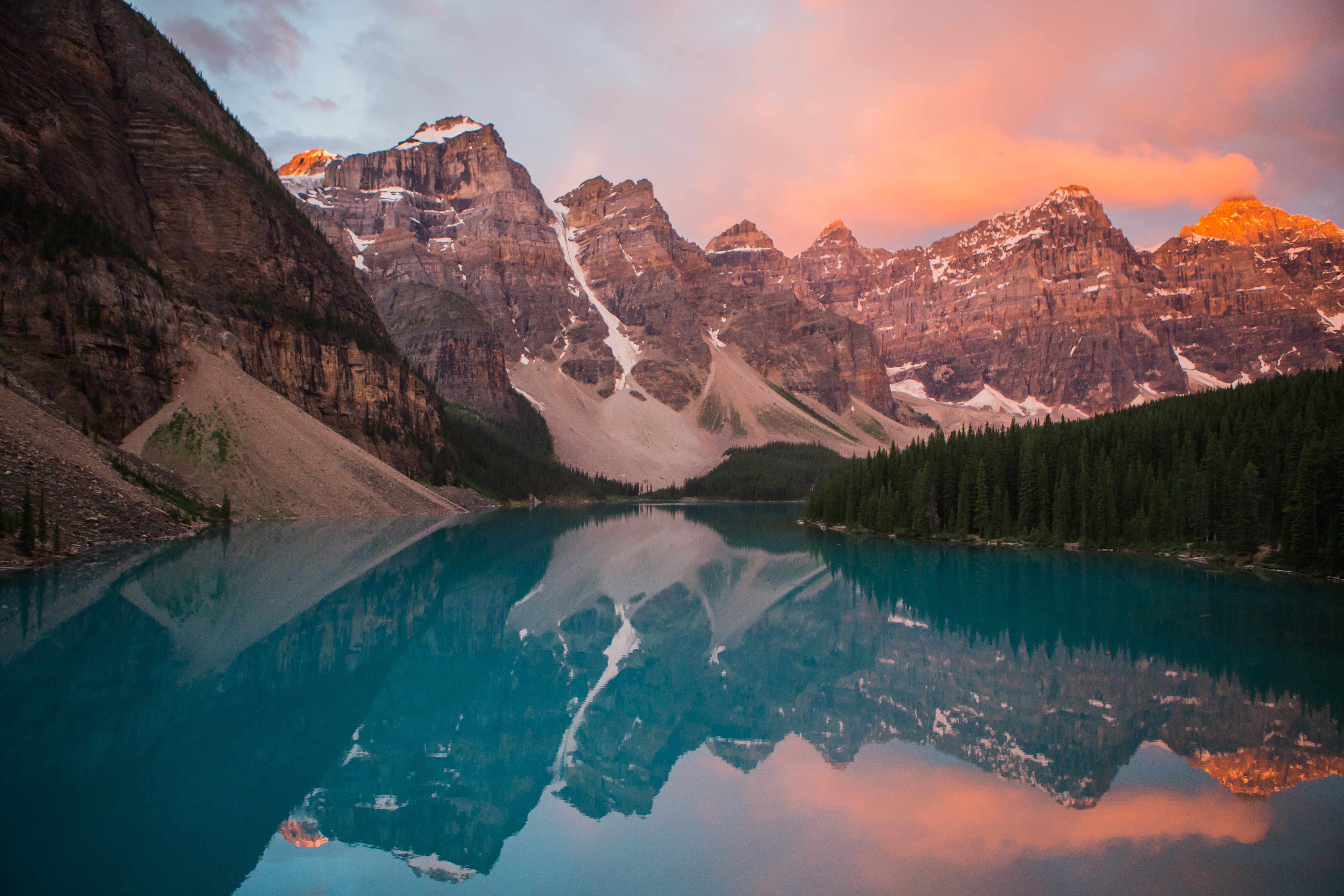 The azure Moraine Lake reflecting nearby mountains during sunset