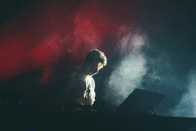 A musician in a white shirt on stage with white and red lights breaking through the smoke behind his...