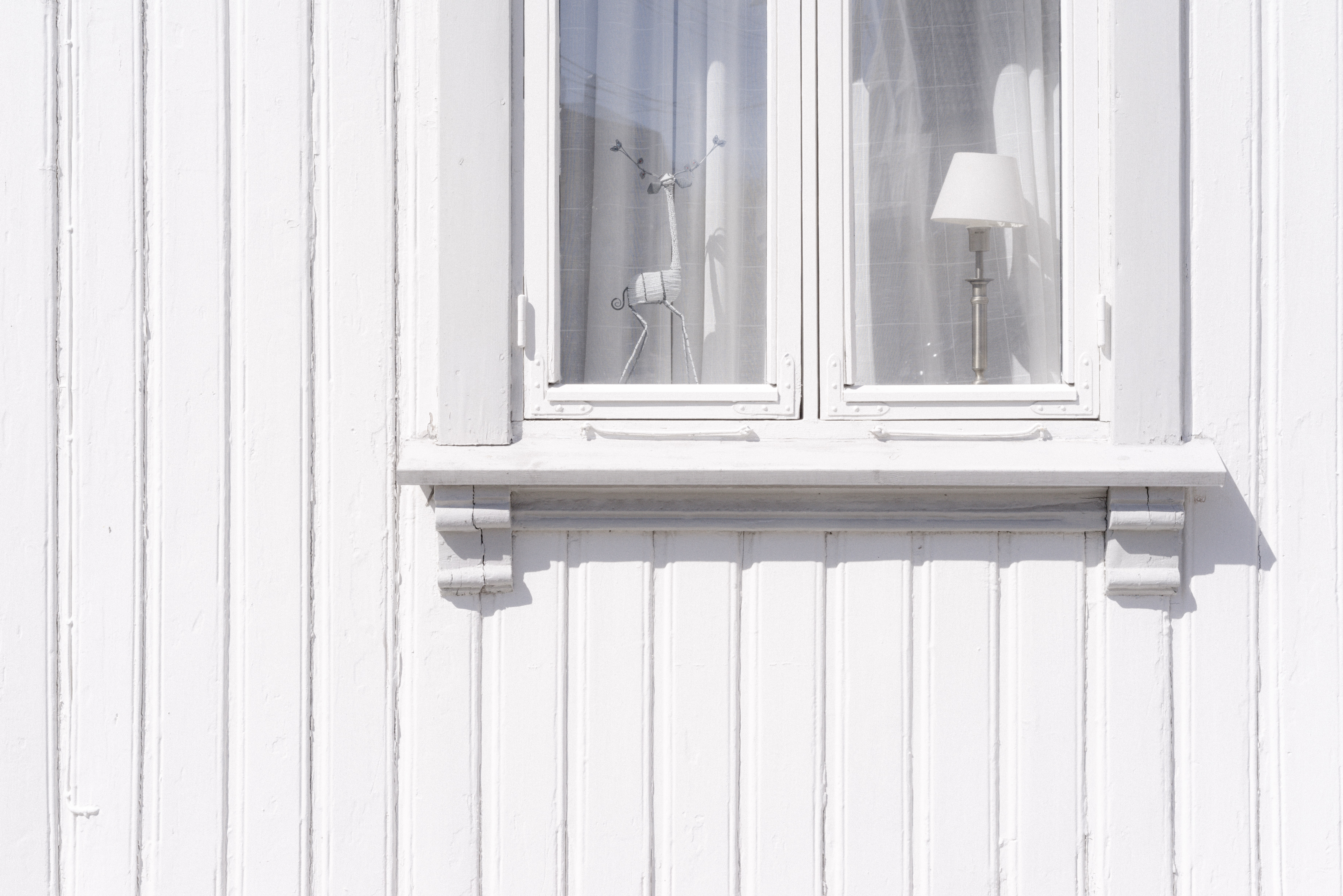 white wooden wall cabinet with figurine and table lamp inside