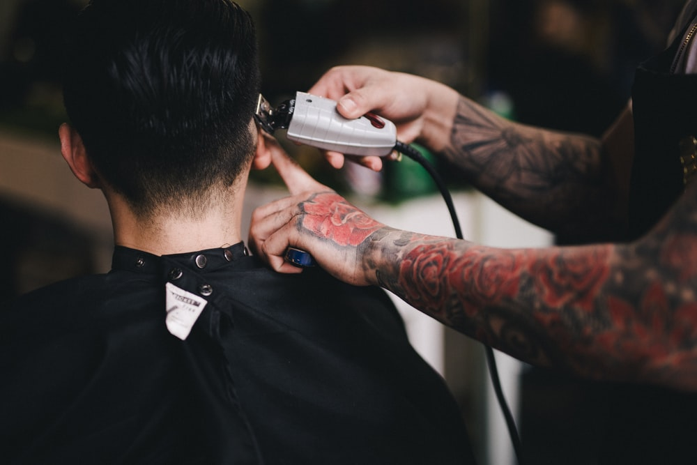 A person in a cape gets their hair shaved by a barber with tattoos