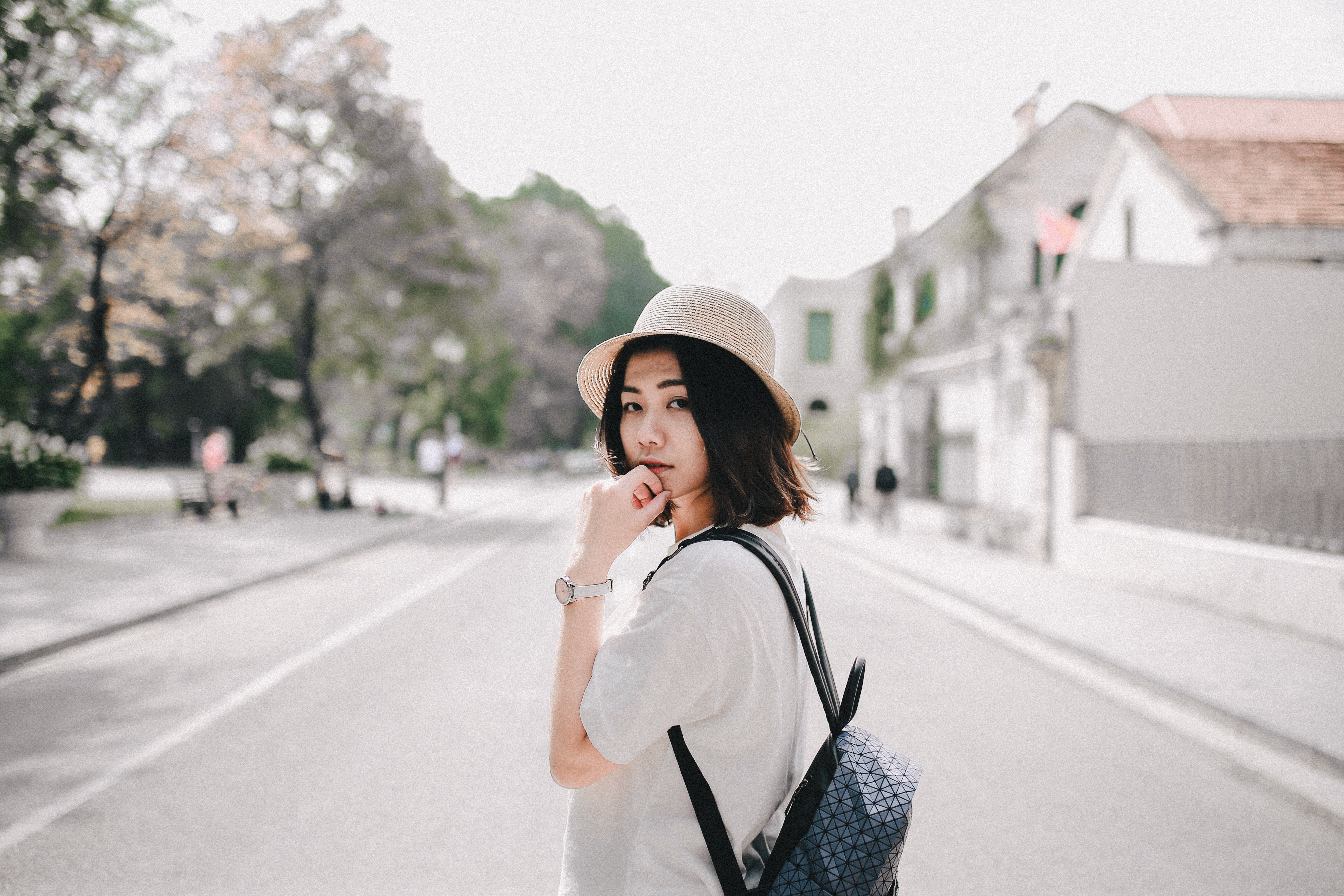 woman wearing white T-shirt and blue backpack standing on road